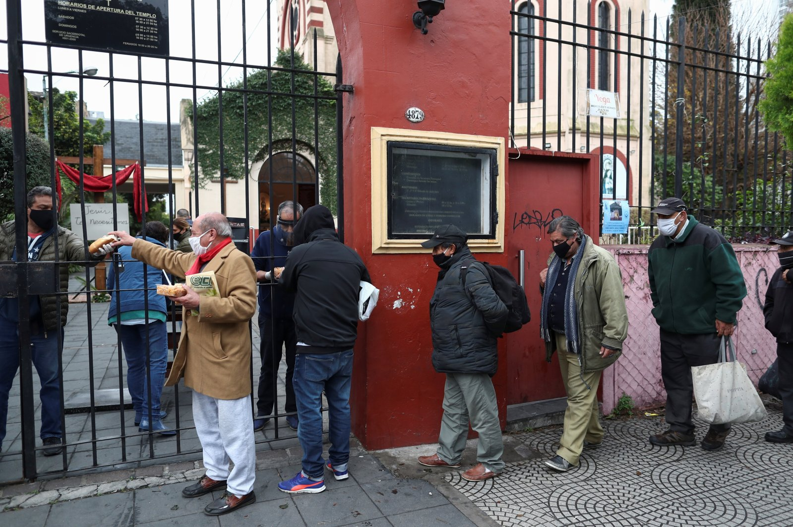 People line up to receive a ration of stew at a soup kitchen organized at the Caacupe church, during the coronavirus outbreak, in Buenos Aires, Argentina, July 23, 2020. (Reuters Photo)