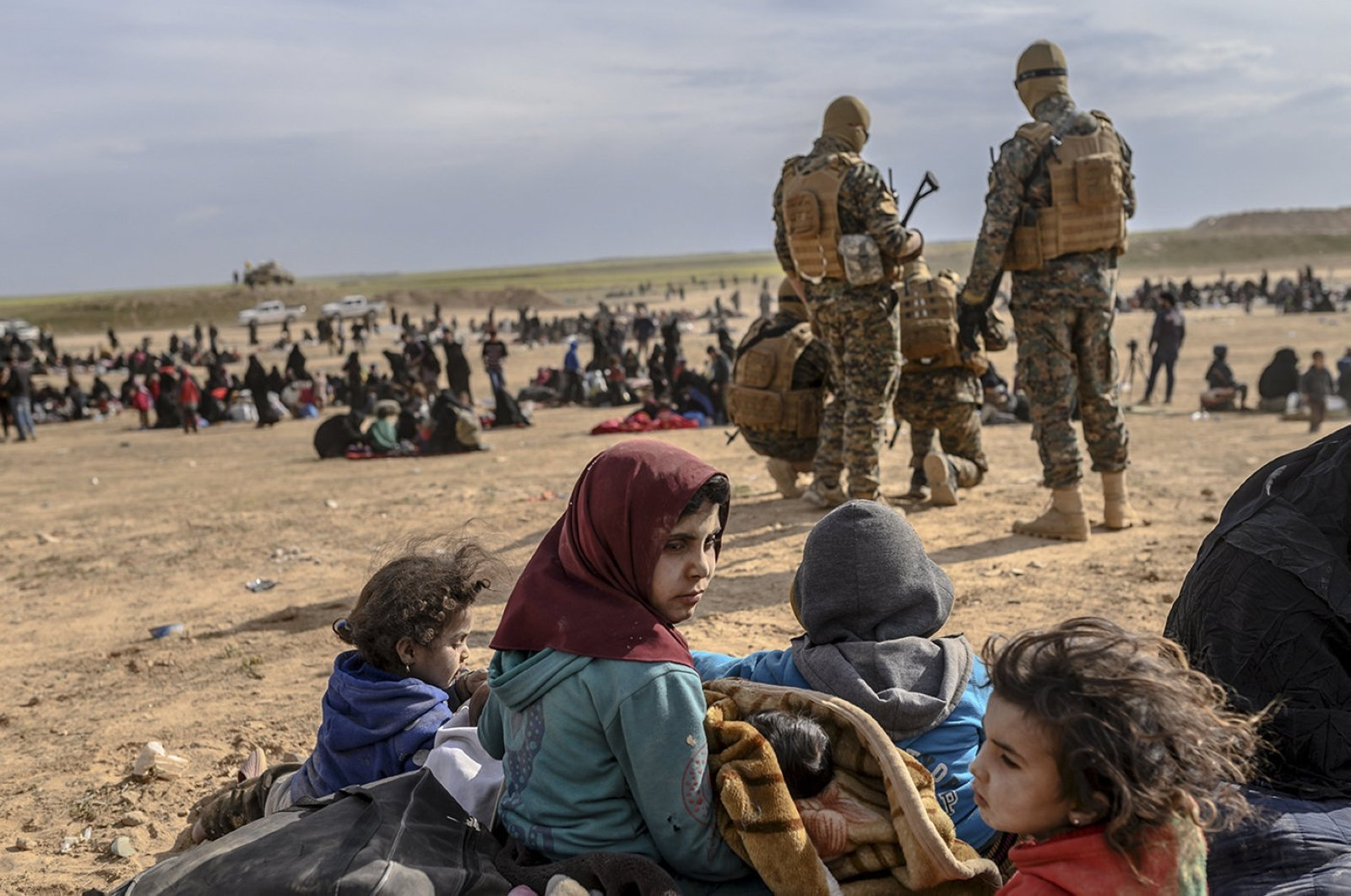 Civilians evacuated from the Daesh terror group's embattled holdout of Baghouz wait at a screening area held by the U.S.-backed YPG/PKK, in the eastern Syrian province of Deir el-Zour, March 5, 2019. (AFP Photo)