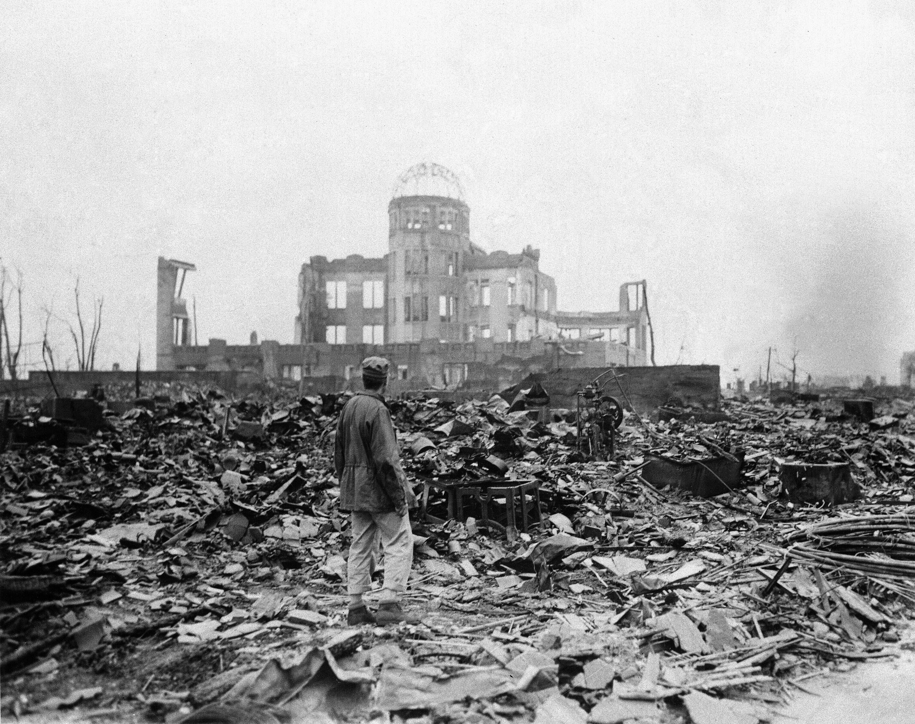 In this Sept. 8, 1945, file photo, an allied correspondent stands in a sea of rubble before the shell of a building that once was a movie theater in Hiroshima, western Japan, a month after the first atomic bomb ever used in warfare was dropped by the U.S. to hasten Japan's surrender. (AP Photo)