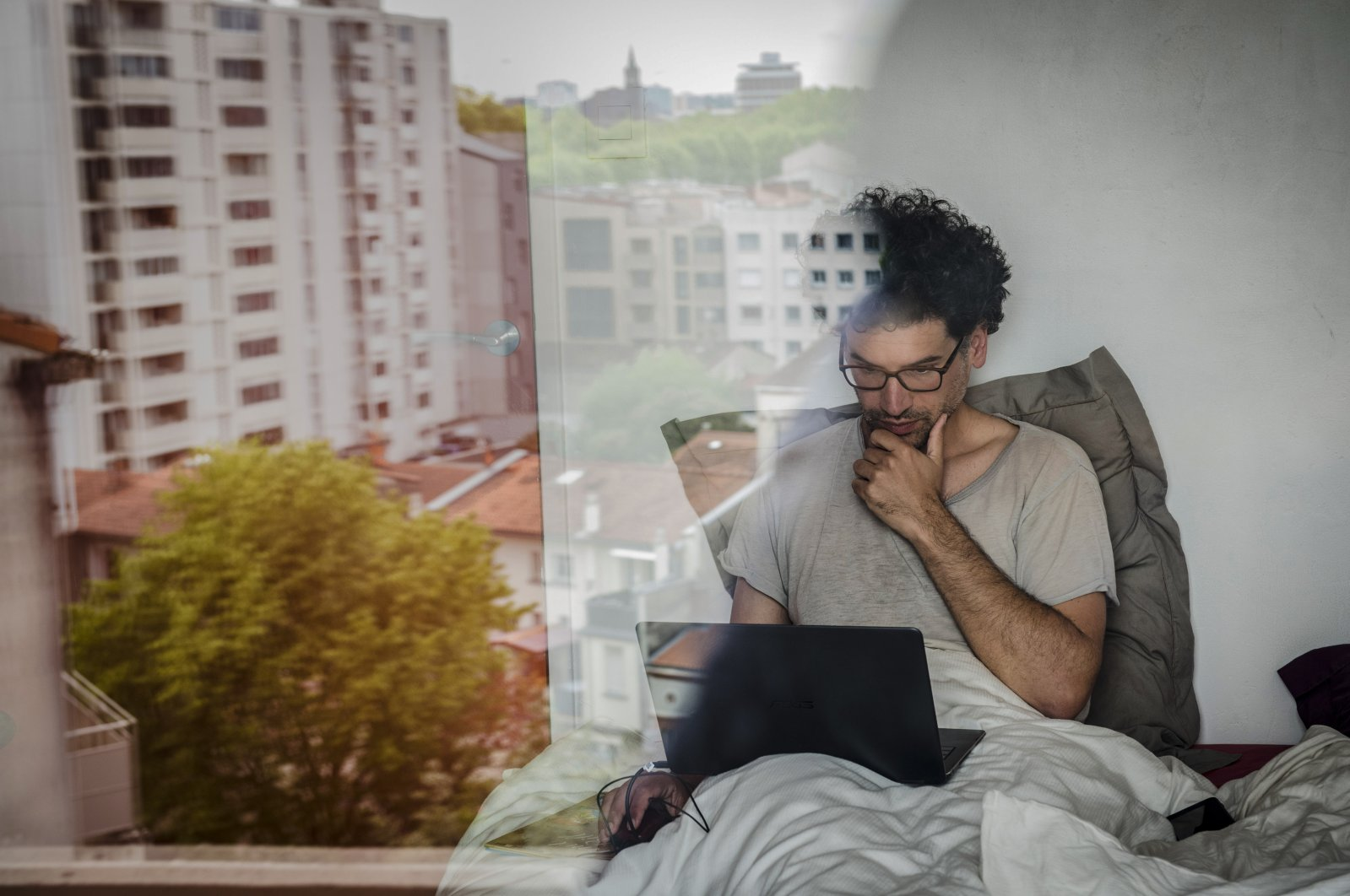 A teacher-researcher works in his bed on his computer in France, on April 18, 2020. (via Reuters)