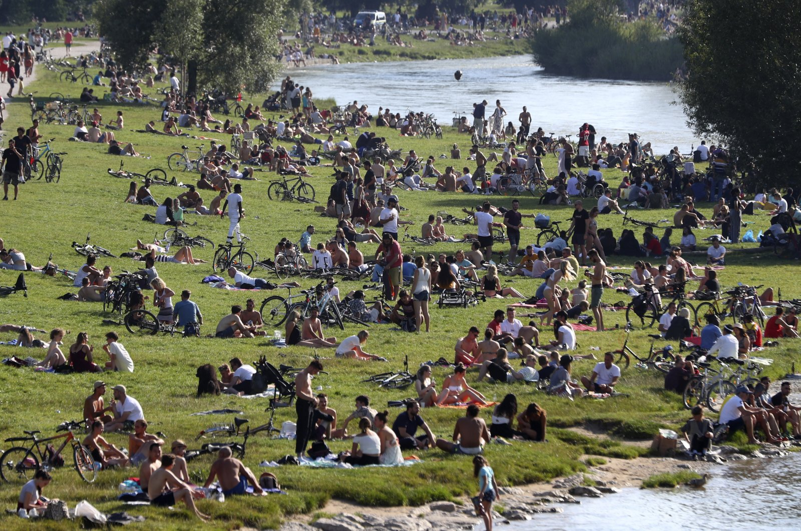Thousands of people enjoy the summer weather on the banks of the Isar river in Munich, Germany, July 19, 2020. (AP Photo)
