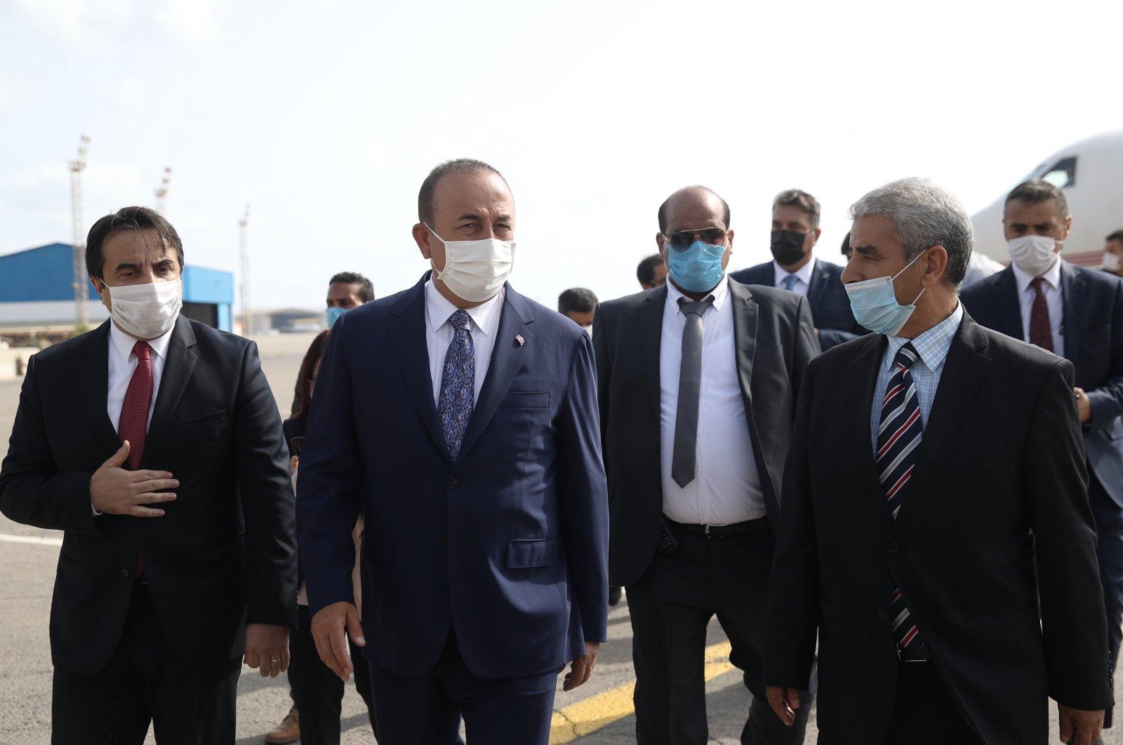 Foreign Minister Mevlüt Çavuşoğlu (C) and Malta's Foreign Minister Evarist Bartolo (R) walk on the tarmac afterlanding in Tripoli, Libya, Aug. 6, 2020. (AA)