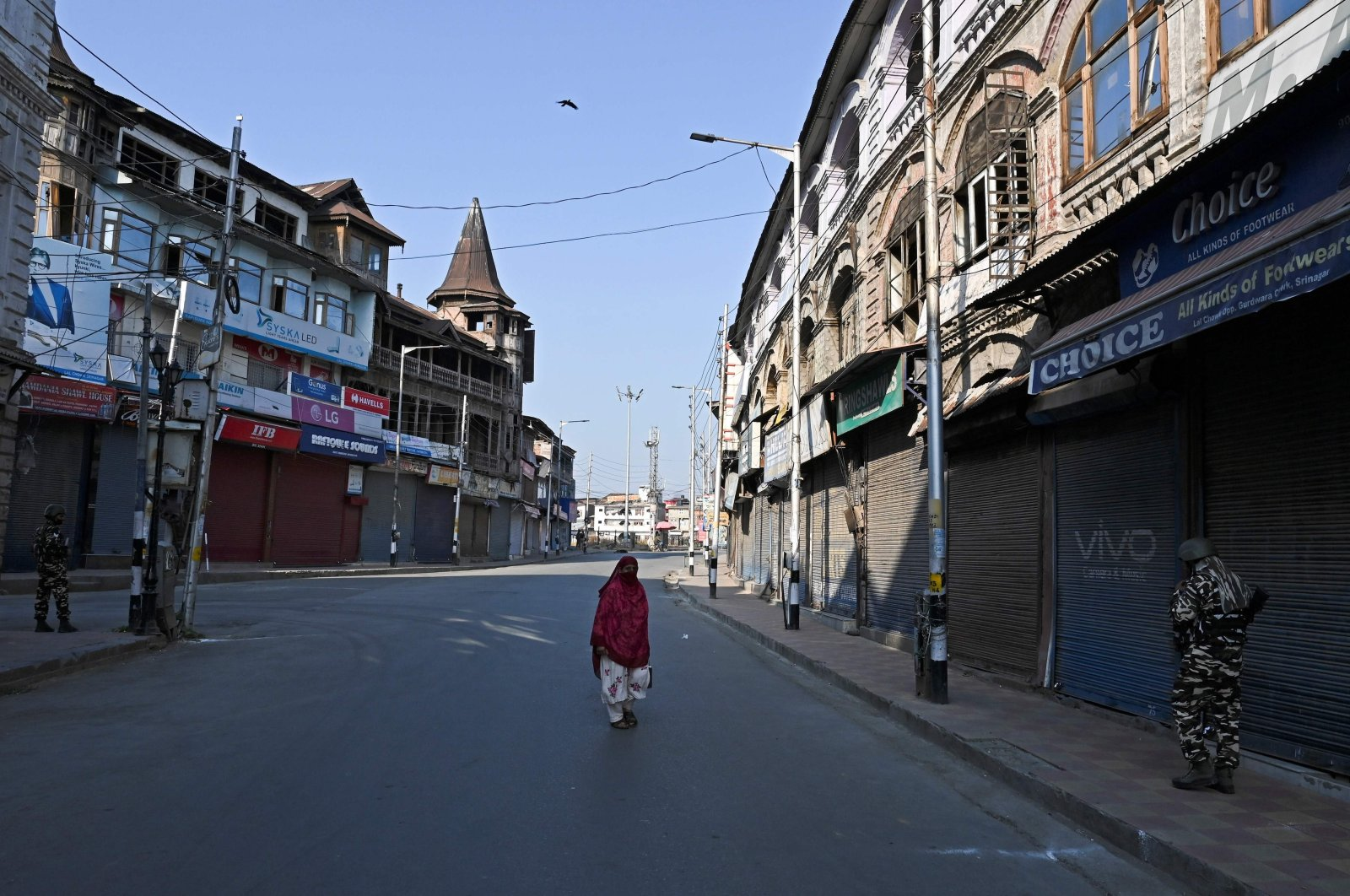 A woman walks along a street as security personnel stand guard during the one-year anniversary of the restive Kashmir region being stripped of its autonomy, Srinagar, Indian-occupied Jammu and Kashmir, Aug. 5, 2020. (AFP Photo)