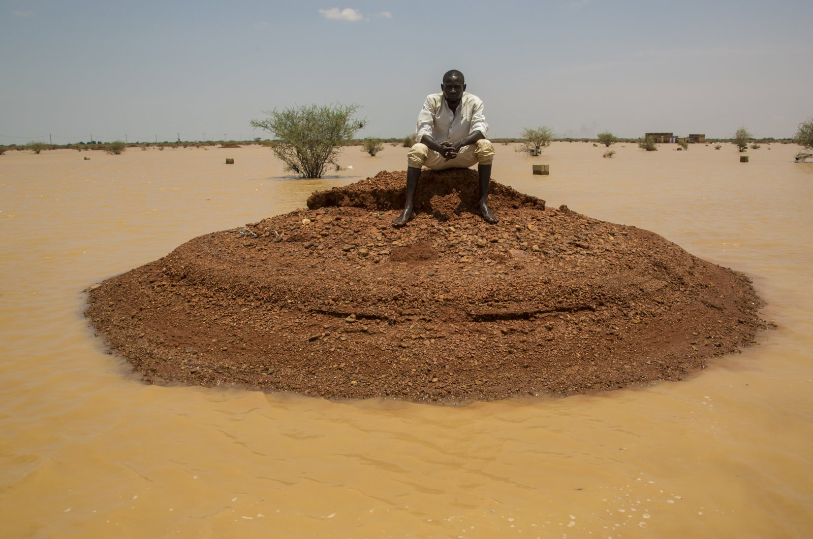 A man sits on a mound of earth surrounded by floodwaters brought on by seasonal torrential rains in the village of Al-Nazile in northeastern Sudan, Aug. 3, 2020. (AA Photo)