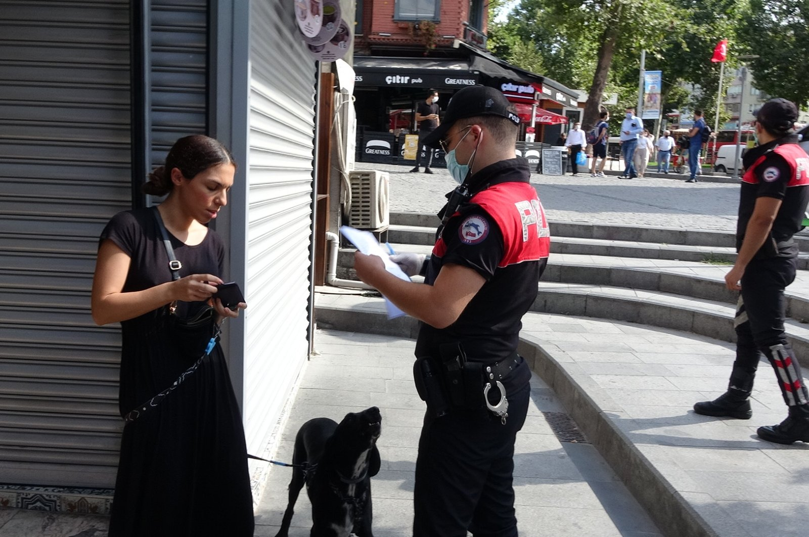 A police officer issues a fine to a woman not wearing a mask in the Beşiktaş district of Istanbul, Turkey, Aug. 6, 2020. (DHA Photo)
