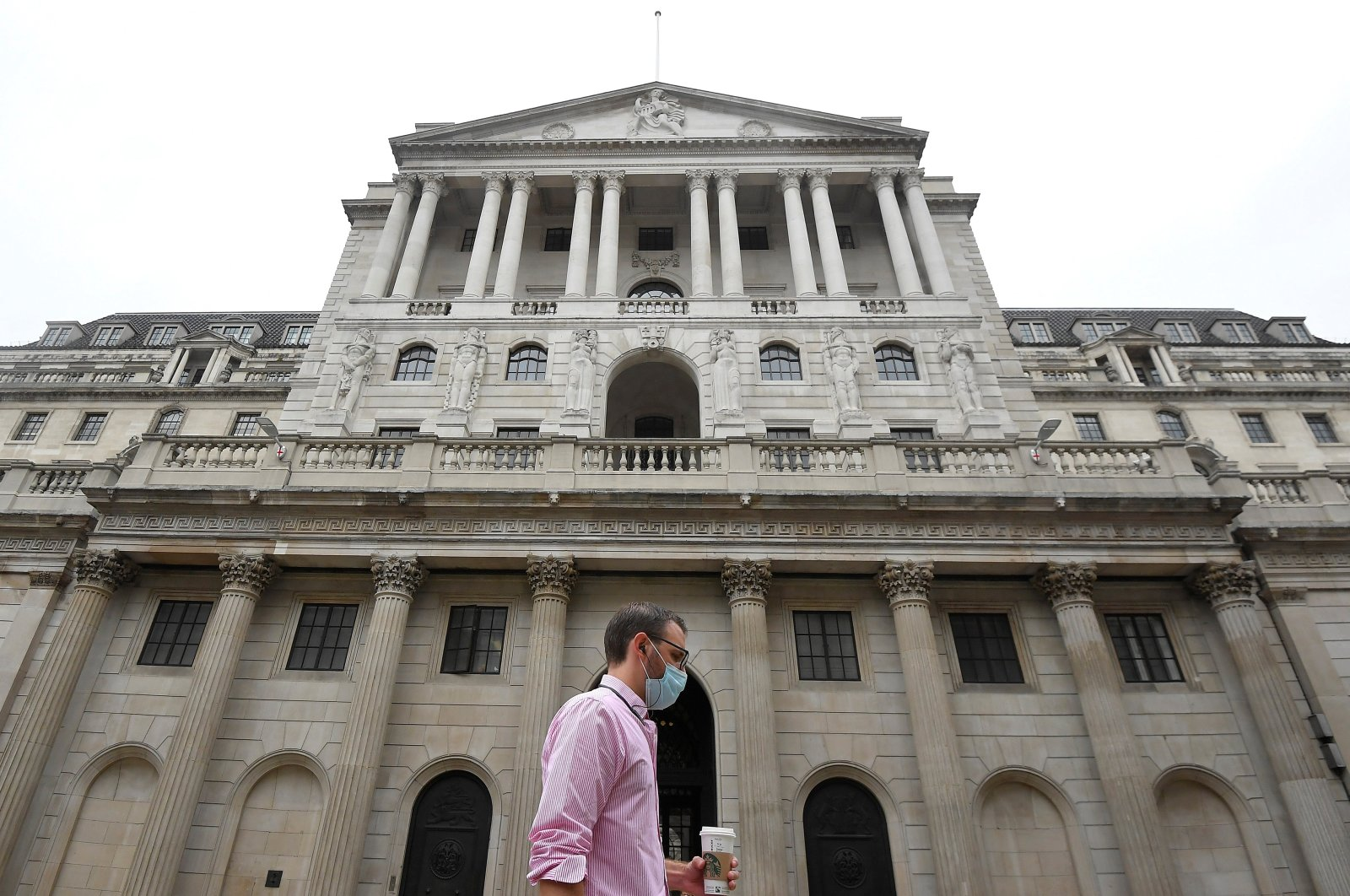 A worker wearing a protective face mask walks past the Bank of England in the City of London, Britain, Aug. 6, 2020. (Reuters Photo)