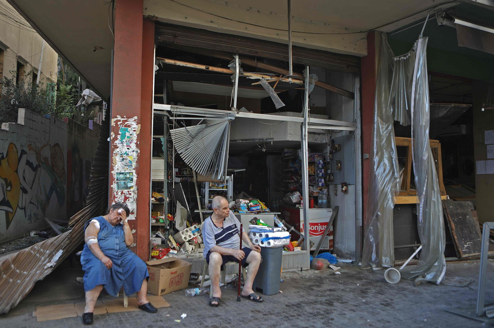 An injured Lebanese woman sits in front of her damaged shop, Beirut, Lebanon, Aug. 5, 2020. (AFP Photo)