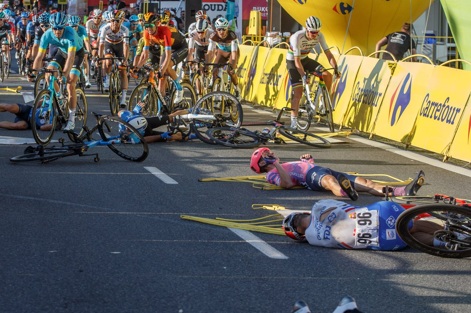 Cyclists lie on the street following a crash in the sprint during the Tour of Poland cycling race, between Chorzow and Katowice, Poland, Aug. 5, 2020. (EPA Photo)