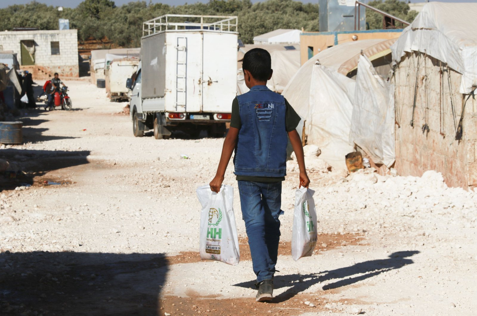 A Syrian boy carries aid received from Turkey's Humanitarian Relief Foundation (IHH) in the northwestern Idlib province of Syria, Aug. 1, 2020. (AA Photo)