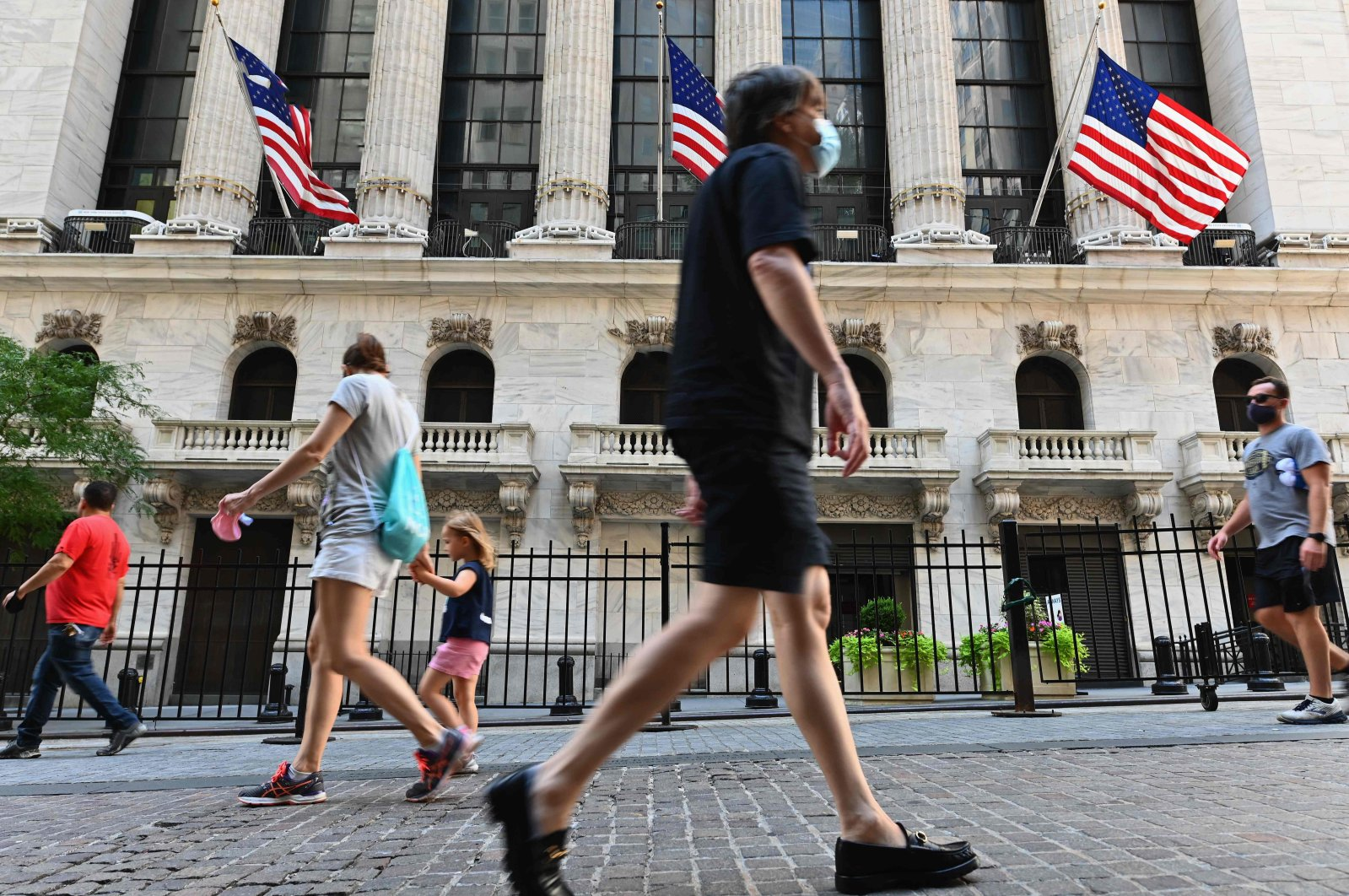 People pass by the New York Stock Exchange (NYSE) at Wall Street in New York City, Aug. 3, 2020. (AFP Photo)