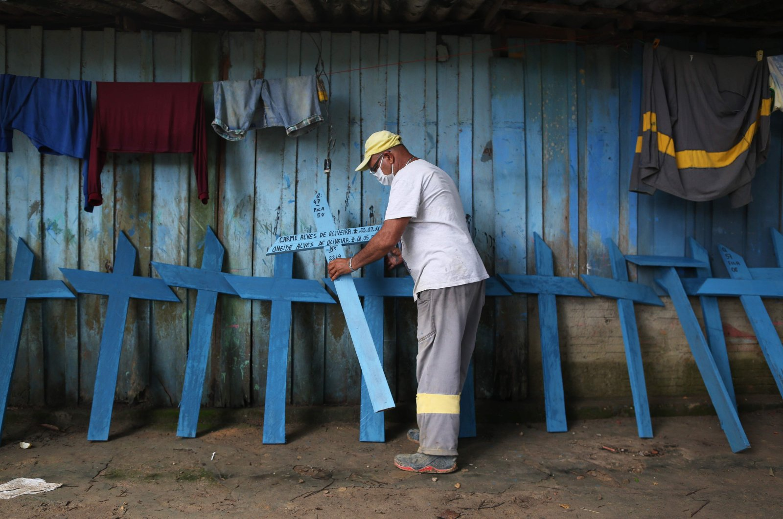 A Brazilian working at Nossa Senhora cemetery places wooden crosses against a wall, Manaus, Brazil, May 08, 2020. (AFP Photo)