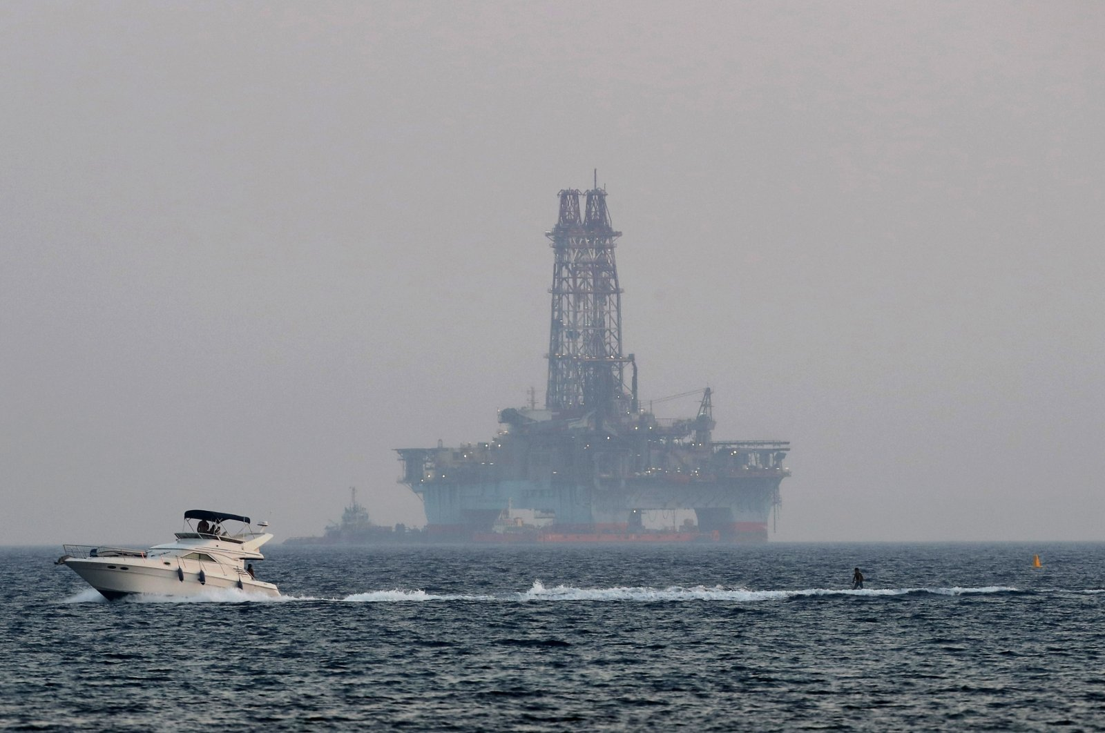 An offshore drilling rig is seen in the waters off Cyprus' coastal city of Limassol as a boat passes with a skier, July 5, 2020. (AP Photo)