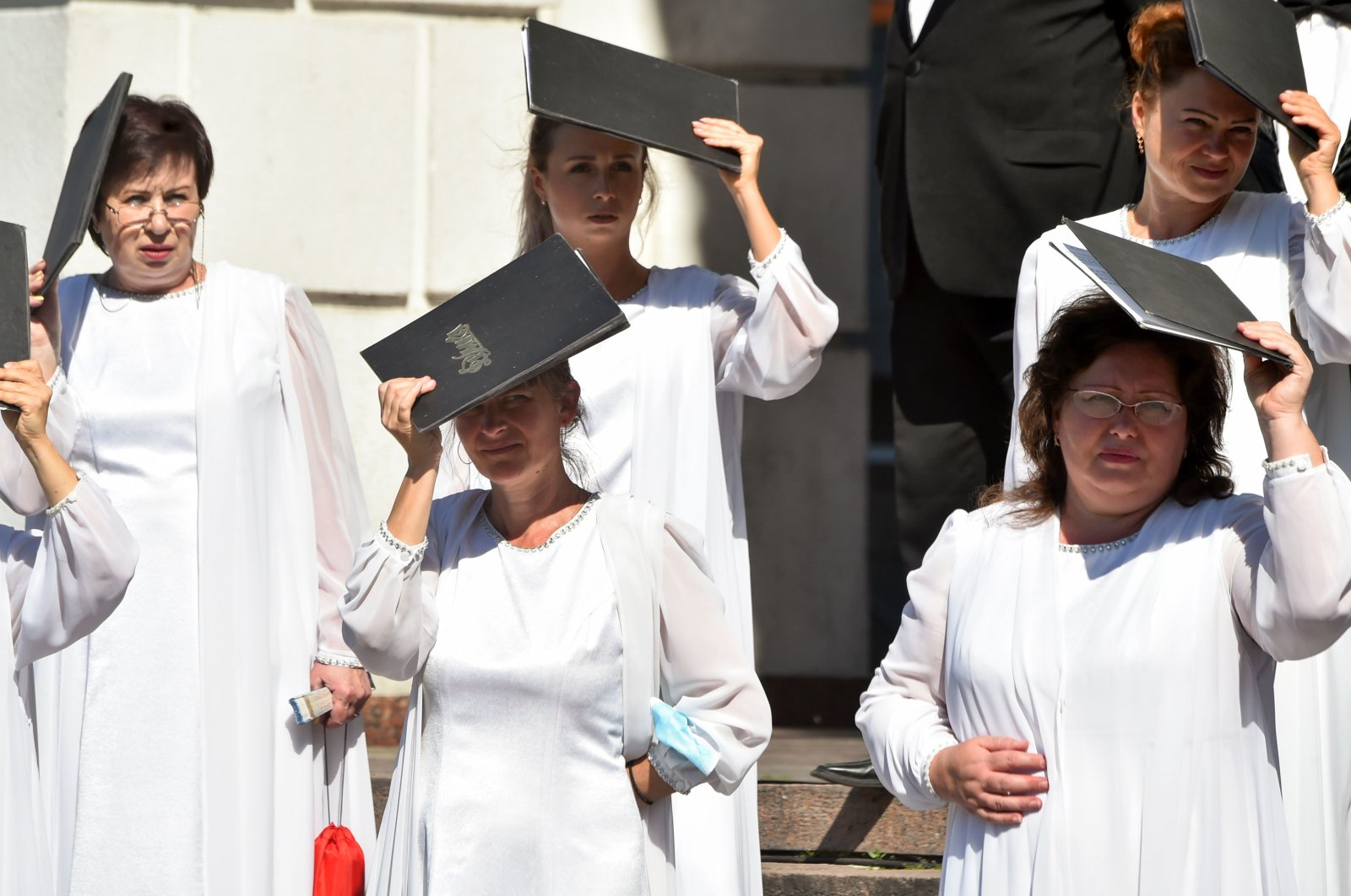 """Choristers of Ukraine's Chapel of """"Dumka"""" protect themselves from the sun with folders and notes during an open-air performance at Kiev's Independence Square during a hot summer day on Aug. 6, 2020. (AFP Photo)"""