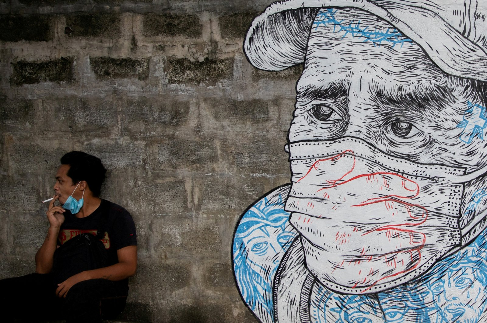 A man smokes a cigarette next to a mural of a man wearing a protective mask amid the COVID-19 outbreak in Quezon City, Metro Manila, Philippines, July 30, 2020. (REUTERS Photo)