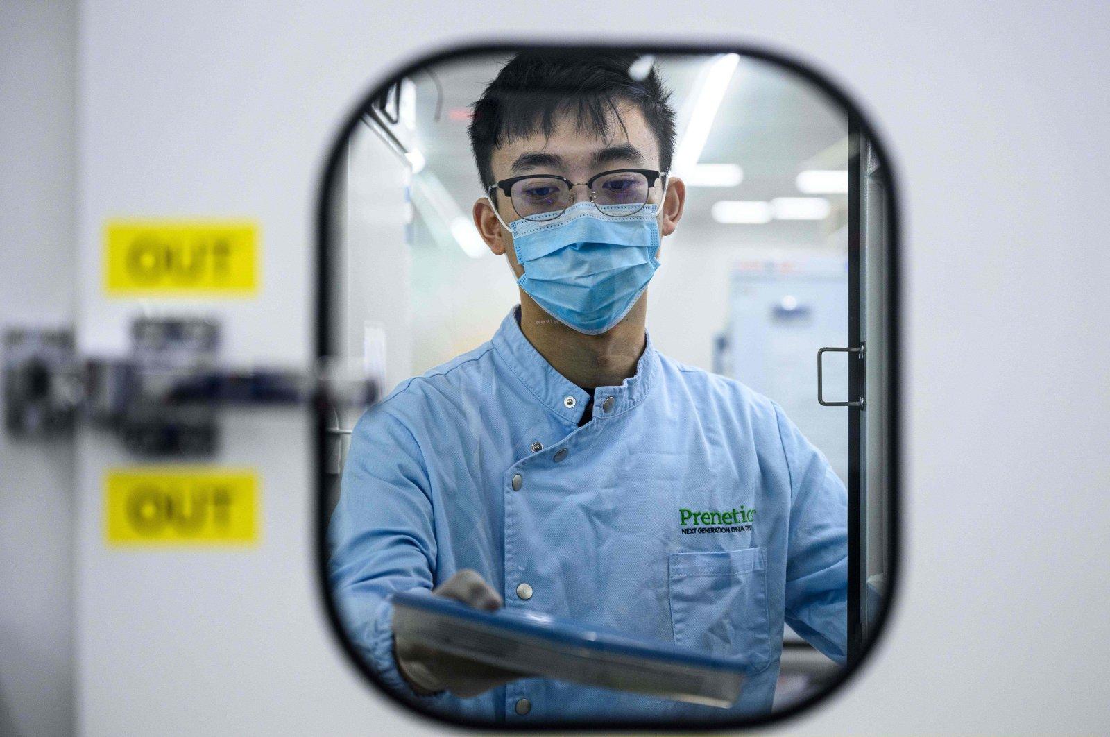 An employee handles a sample at a laboratory of biotech startup Prenetics/Circle DNA in Hong Kong, June 5, 2020. (AFP Photo)