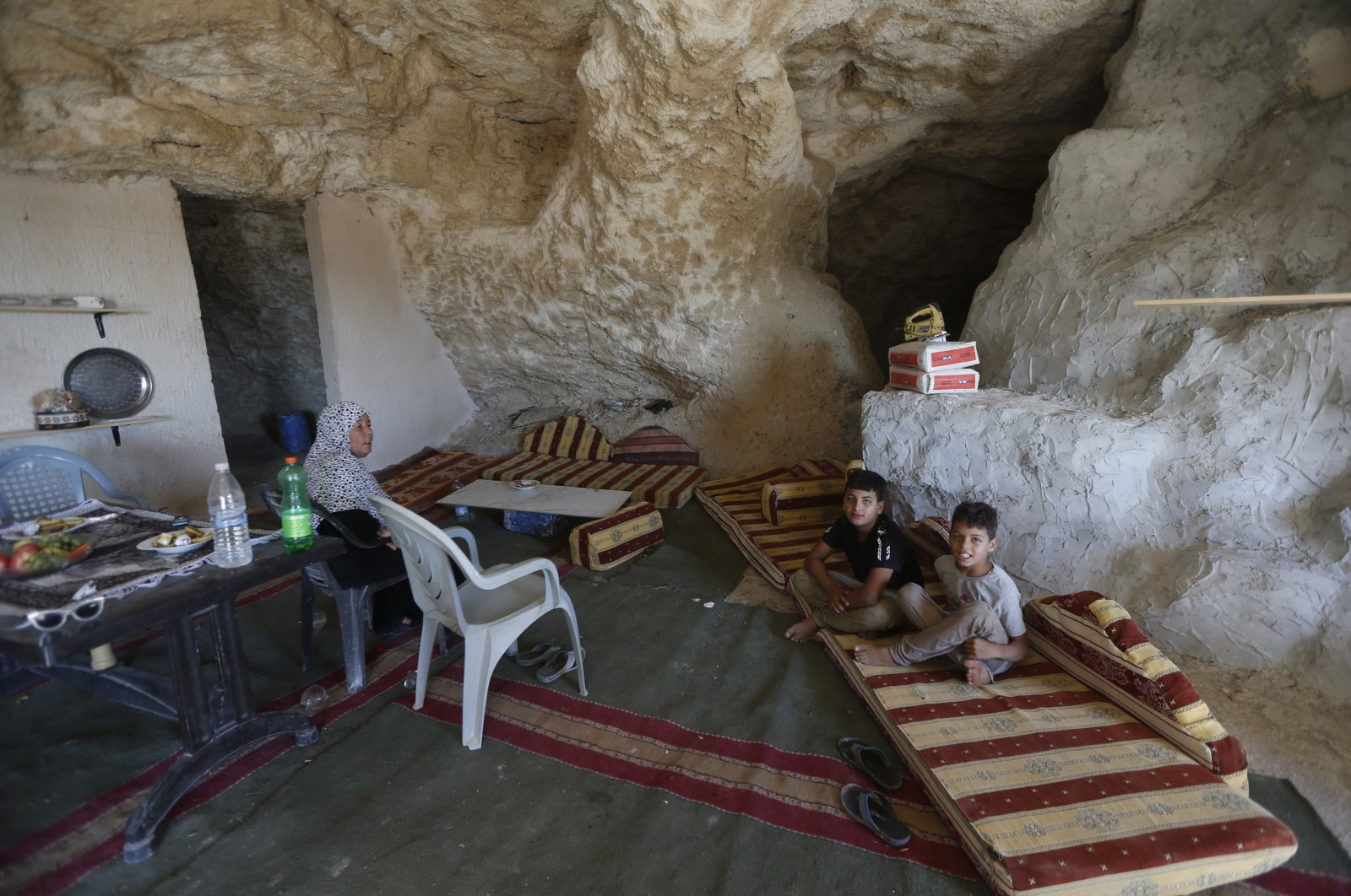 Members of a Palestinian family sit inside a cave they use as their home on the outskirts of the West Bank City of Jenin, Palestine, Aug. 1, 2020. (EPA Photo)