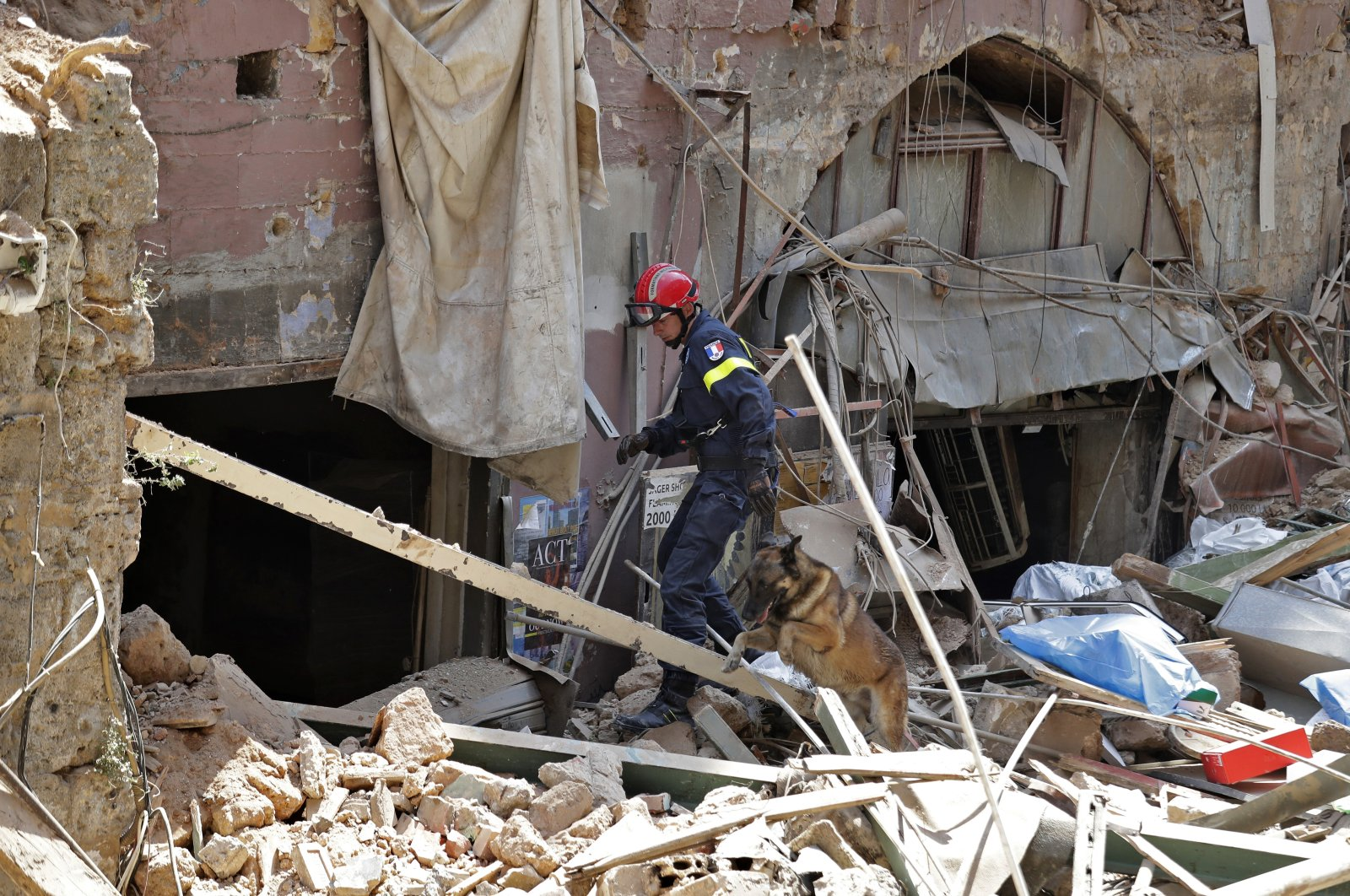A French fireman and a rescue dog search in the rubble of a building after the Tuesday explosion at the seaport of Beirut, in Beirut, Lebanon, Thursday, Aug. 6, 2020. (AP Photo)