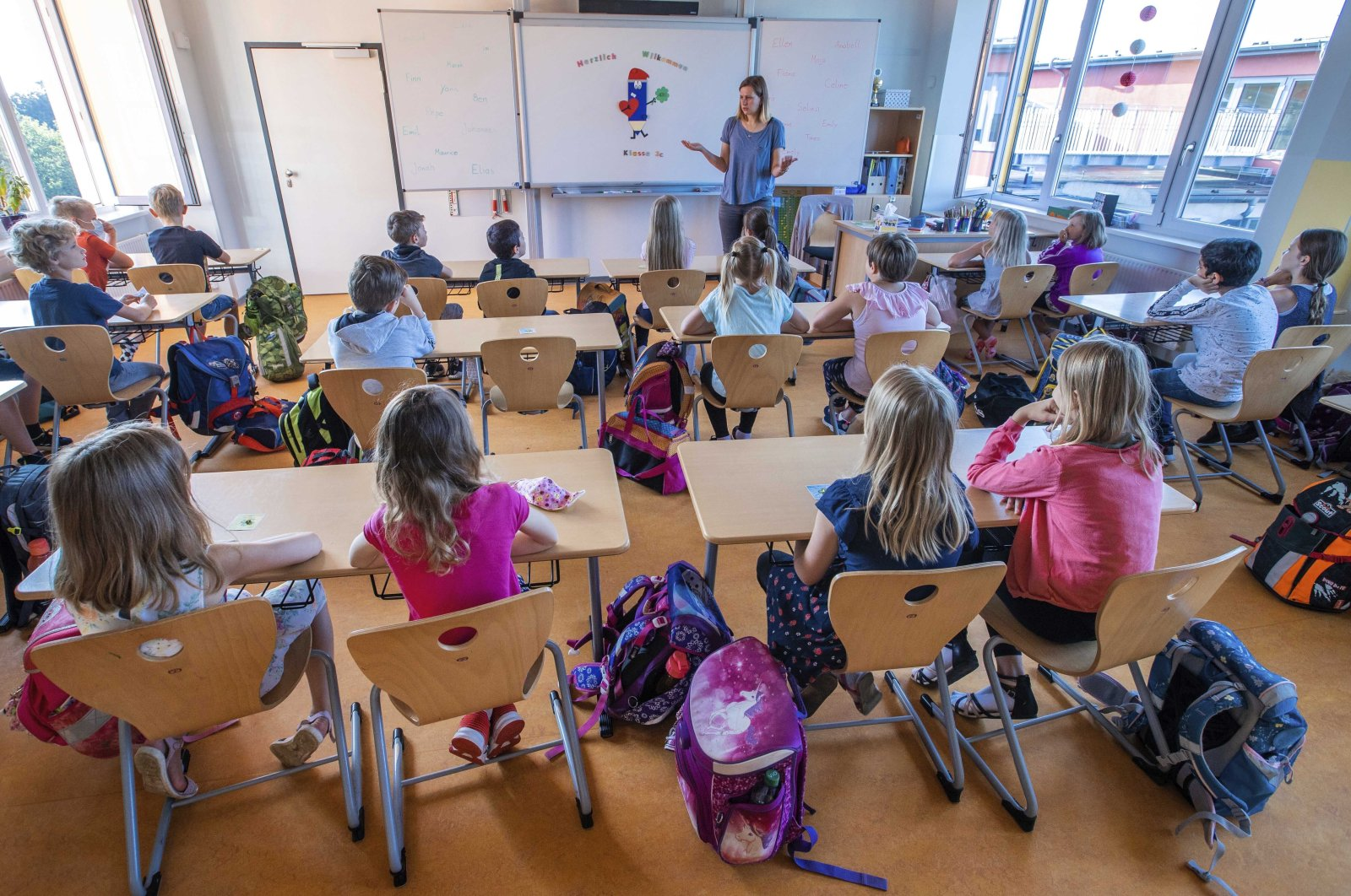 Teacher Francie Keller welcomes his pupils to the Lankow primary school on the first day of school in Schwerin, Germany, Aug. 3, 2020. (AP Photo)