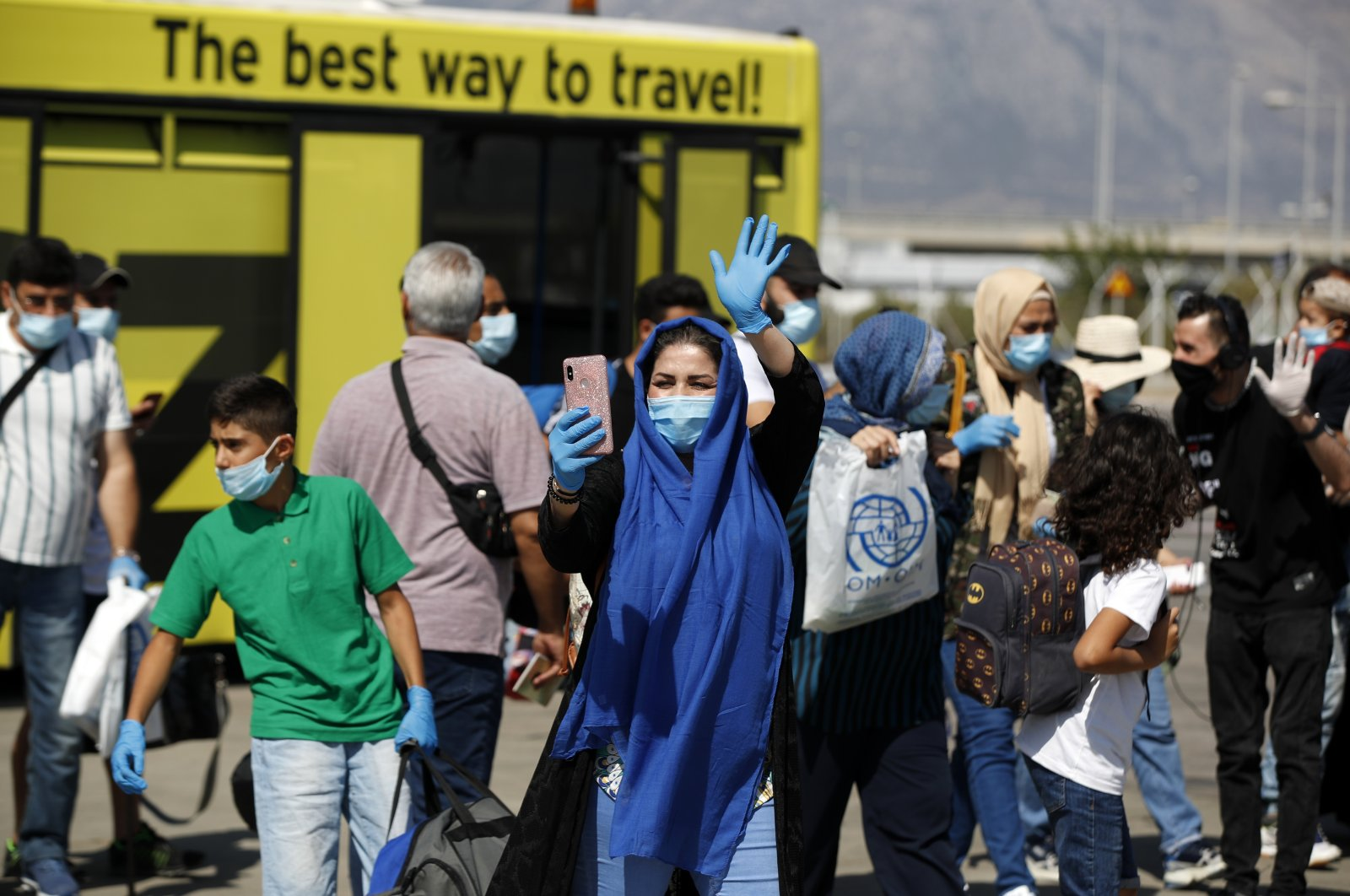A migrant wearing a face mask to prevent the spread of coronavirus, waves before boarding an airplane bound for Iraq at the Eleftherios Venizelos International Airport in Athens, Aug. 6, 2020. (AP Photo)