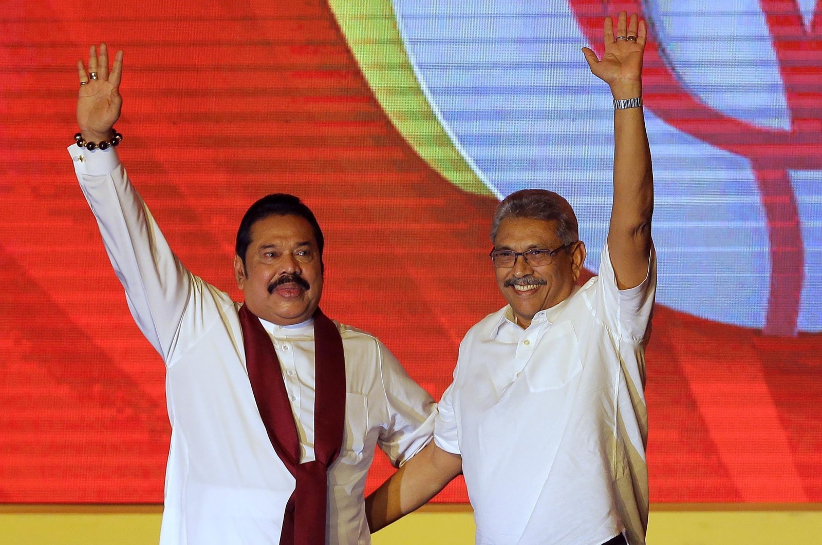 Former Sri Lankan President Mahinda Rajapaksa (L) and former Defense Secretary and his brother Gotabaya Rajapaksa wave at supporters during a party convention held to announce the presidential candidacy, Colombo, Aug. 11, 2019. (AP Photo)