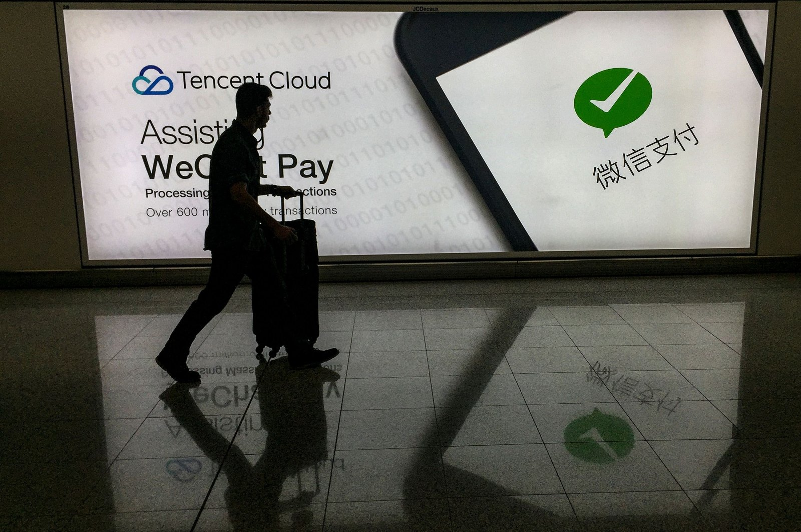 This Aug. 21, 2017 file photo shows a man walking at Hong Kong's international airport past an advertisement for the WeChat social media platform, owned by China's Tencent. (AFP Photo)