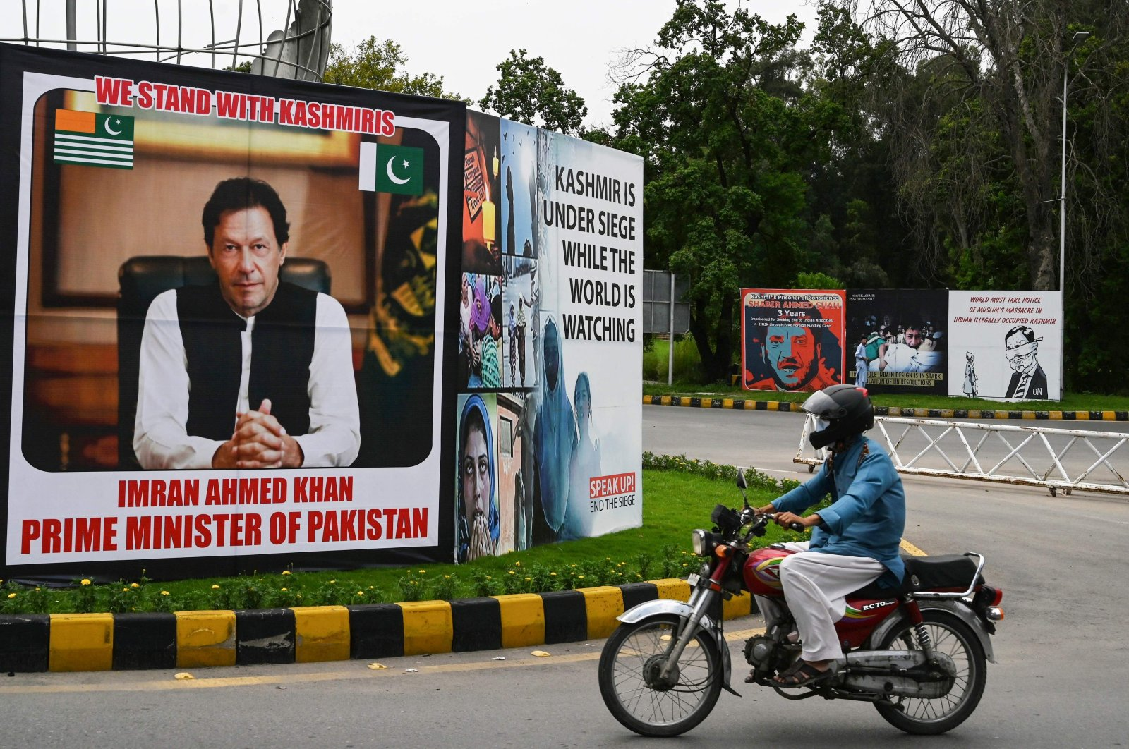 A motorcyclist rides past a billboard displaying a picture of Pakistan's Prime Minister Imran Khan along a street in Islamabad, Aug. 4, 2020. (AFP Photo)