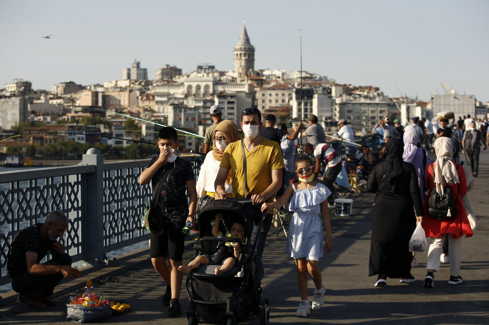 People walk along the Galata Bridge, with the historical Galata Tower in the background, in Istanbul, Friday, Aug. 7, 2020. (AP Photo)