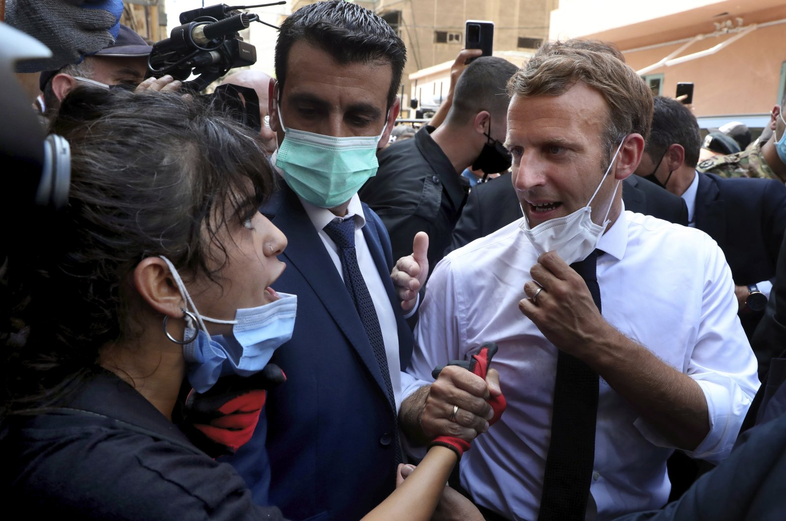 French President Emmanuel Macron (R), speaks with a woman as he visits the Gemayzeh neighborhood, which suffered extensive damage from an explosion on Tuesday that hit the seaport of Beirut, Lebanon, Aug. 6, 2020. (AP Photo)