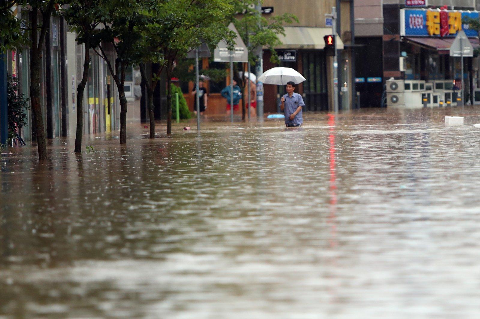 A resident wades through a flooded street amid heavy rain in Gwangju, South Korea, Aug. 8, 2020. (EPA Photo)