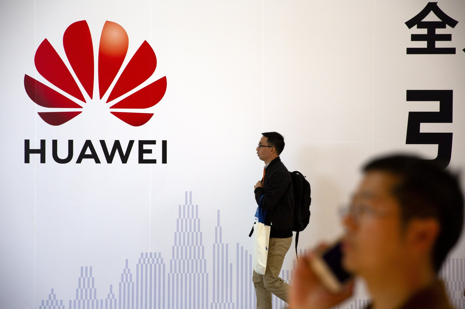 A man uses his smartphone as he stands near a billboard for Chinese technology firm Huawei at the PT Expo in Beijing, China on Oct. 31, 2019. (AP Photo)