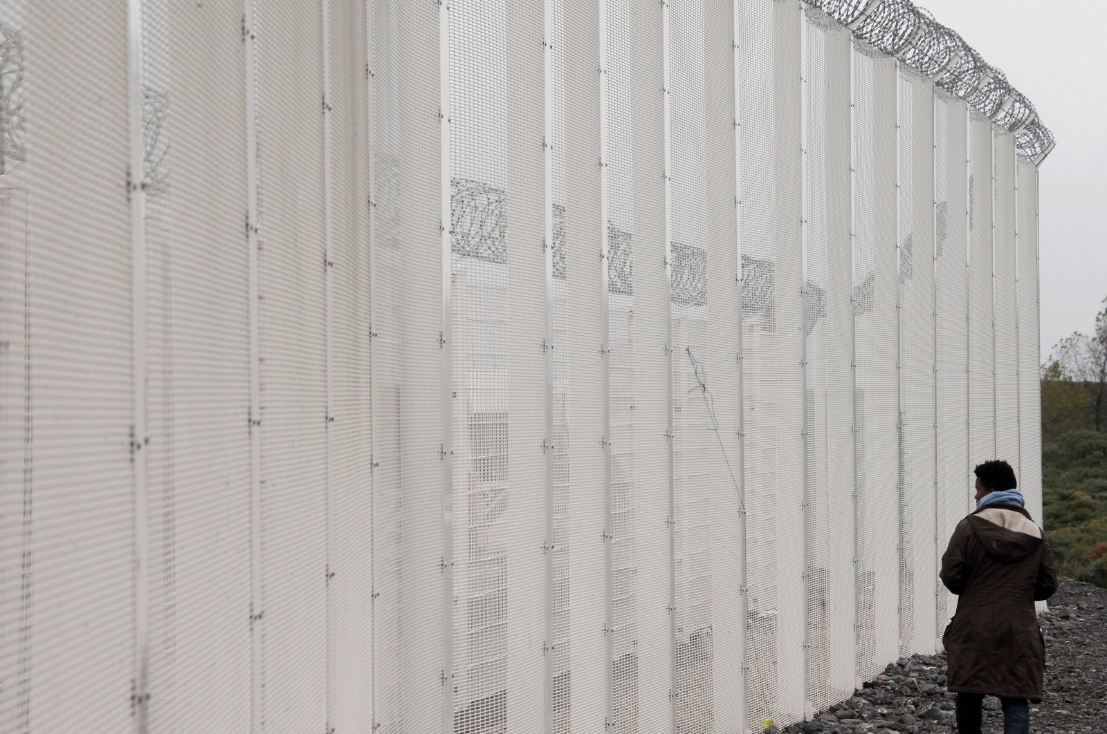 A migrant stands near a fence installed to secure the Eurotunnel platform area near the migrant camp known as the new Jungle in Calais, northern France, Oct. 21, 2015. (AP Photo)
