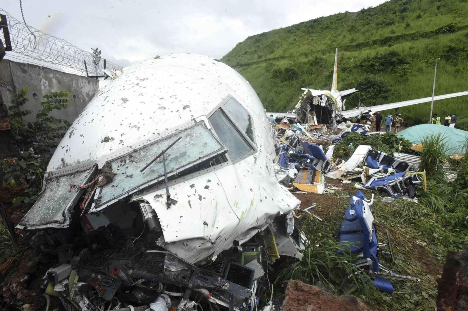 People stand by the debris of the Air India Express flight that skidded off a runway while landing in Kozhikode, Kerala state, India, Saturday, Aug. 8, 2020. (AP Photo)