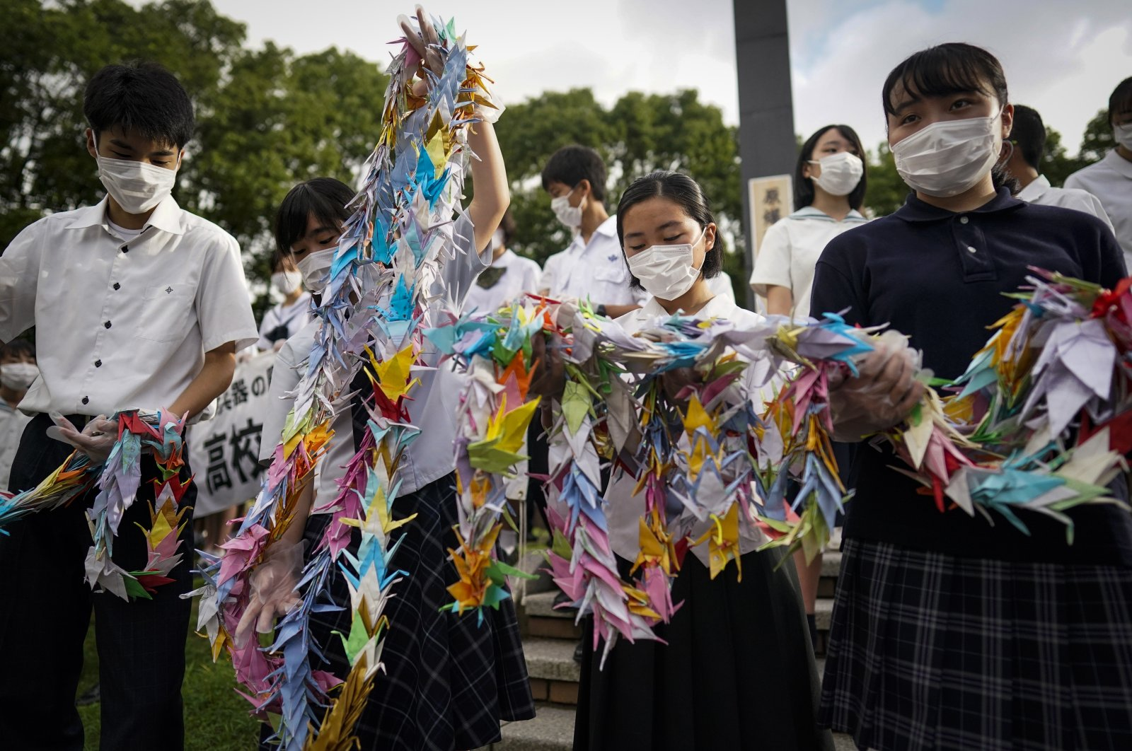 Highschool students offer Senbazuru, or One Thousand Paper Cranes, to the victims of the atomic bombing at Hypocenter park in Nagasaki, southern Japan, 09 August 2020. (EPA Photo)