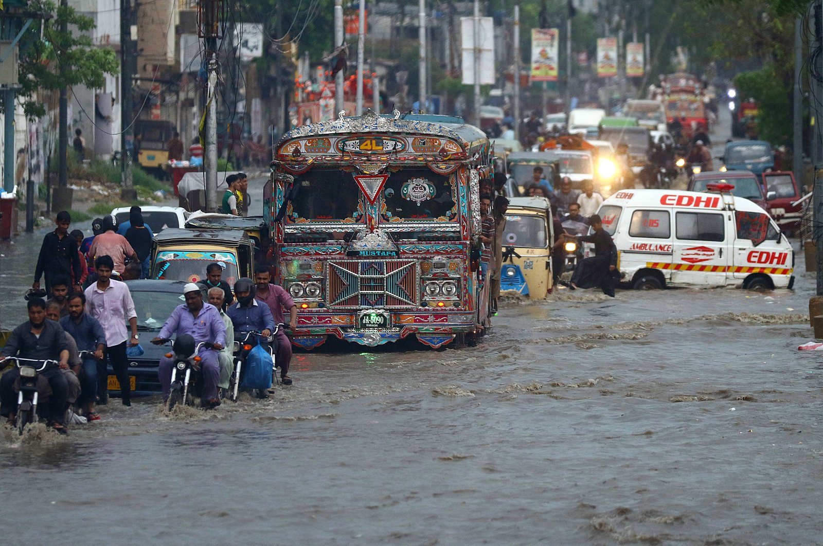 People make their way through a flooded road after monsoon rains in Karachi, Pakistan, 07 August 2020. (EPA Photo)