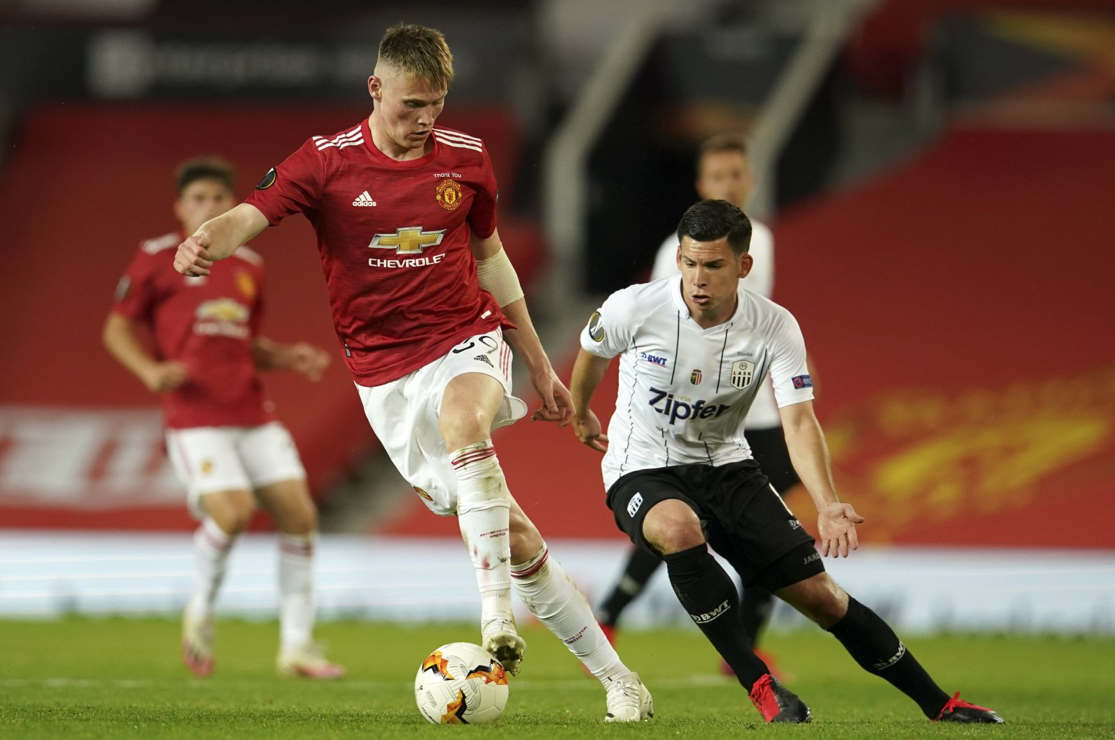 Manchester United's Scott McTominay (L), and LASK's Peter Michorl battle for the ball during the Europa League round of 16, second leg match in Manchester, England, Aug. 5, 2020. (AP Photo)