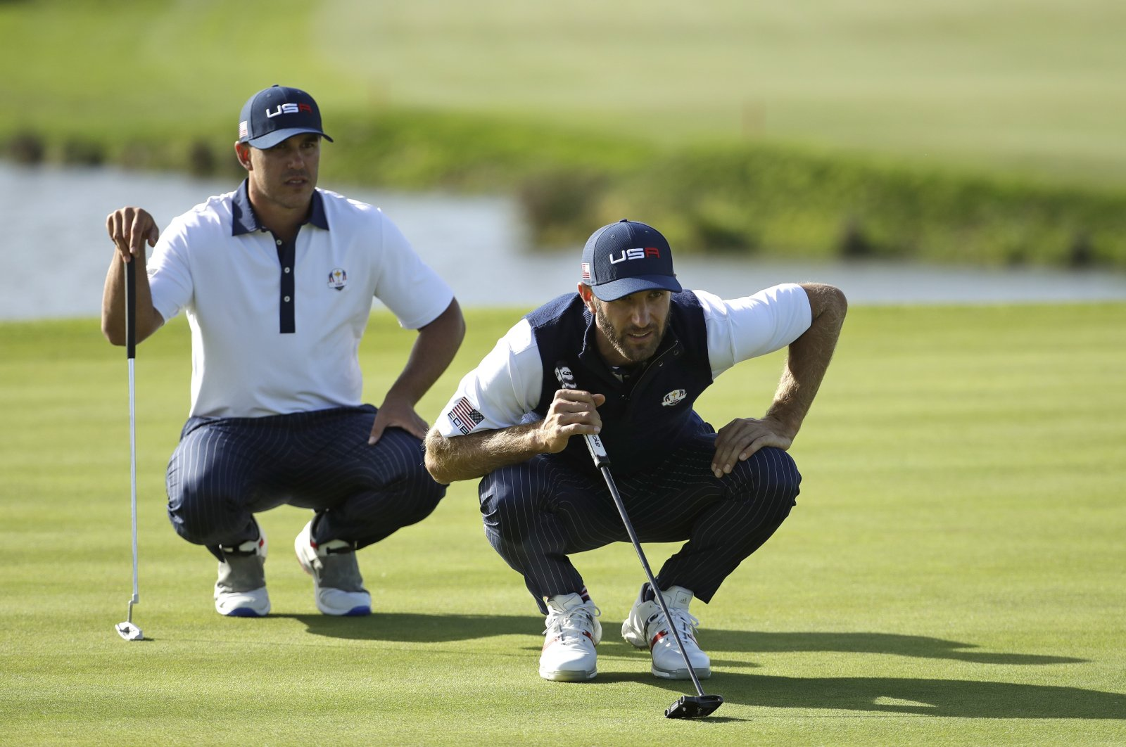 Dustin Johnson (R) and Brooks Koepka line up a putt during a foursome match on the second day of the 42nd Ryder Cup at Le Golf National in Saint-Quentin-en-Yvelines, outside Paris, France, Sept. 29, 2018. (AP Photo)