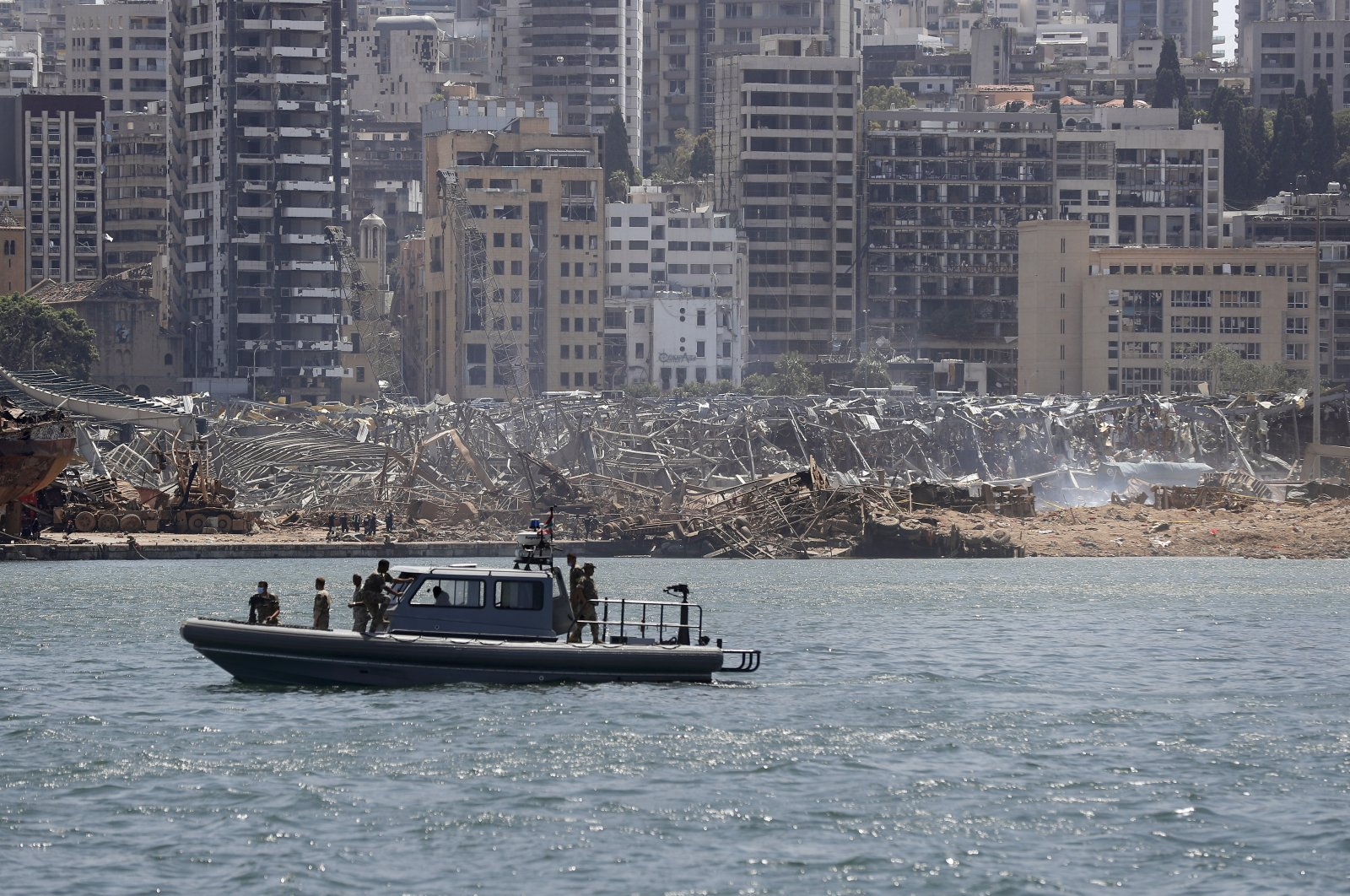 Lebanese navy patrol the sea in front of damaged resident buildings and the destroyed port warehouses at the scene of Tuesday's explosion that hit the seaport of Beirut, Lebanon, Saturday, Aug. 8, 2020. (AP Photo)