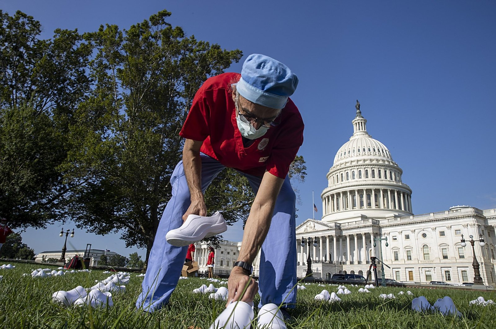 Scott Weinstein, a nurse at Washington Hospital places nurses shoes during a Vigil For Nurses Who've Died From Covid-19 at the U.S. Capital on July 21, 2020 in Washington, DC. (AFP Photo)