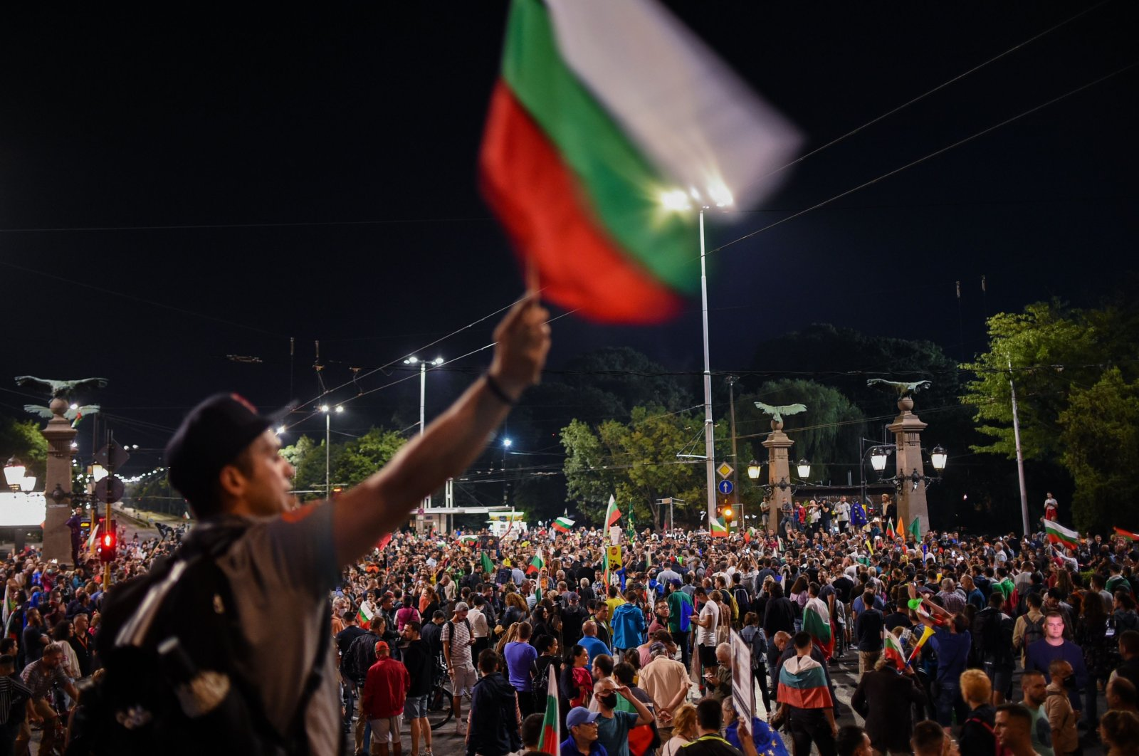 A protester waves the Bulgarian flag as people gather on a major crossroads in downtown Sofia during an anti-government demonstrations on Aug. 7, 2020,. (AFP Photo)