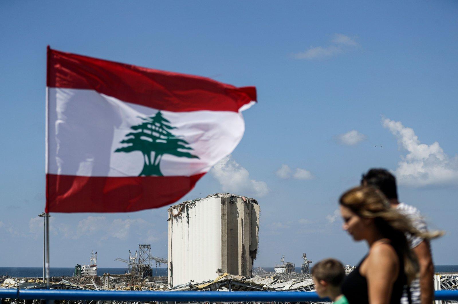 People walk along a bridge past a Lebanese flag flying near the port of Lebanon's capital Beirut as damaged grain silos in the background, Beirut, Lebanon, Aug. 9, 2020. (AFP Photo)
