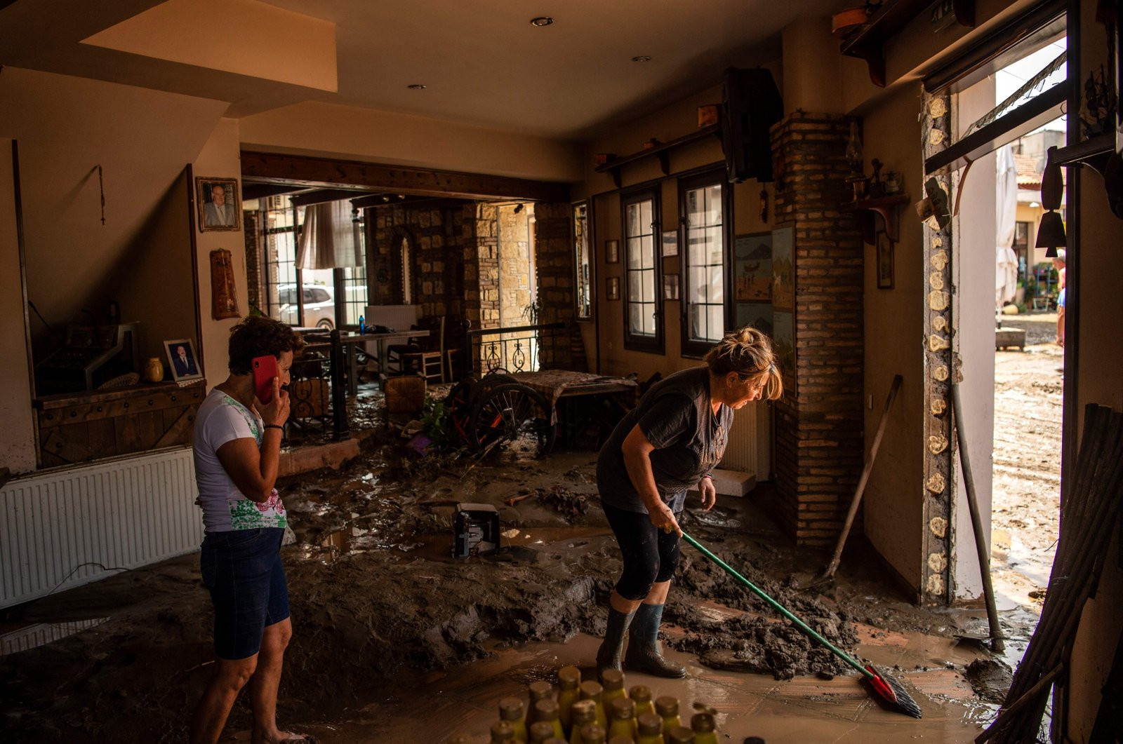 People try to move away water and mud from their shop, following a storm at the village of Politika, on Evia island, northeast of Athens, Greece, Aug. 9, 2020. (AFP Photo)