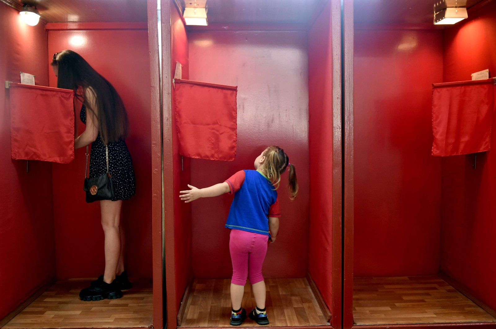 A girl looks into a voting booth at a polling station during the presidential election in Minsk, Belarus, Aug. 9, 2020. (AFP Photo)