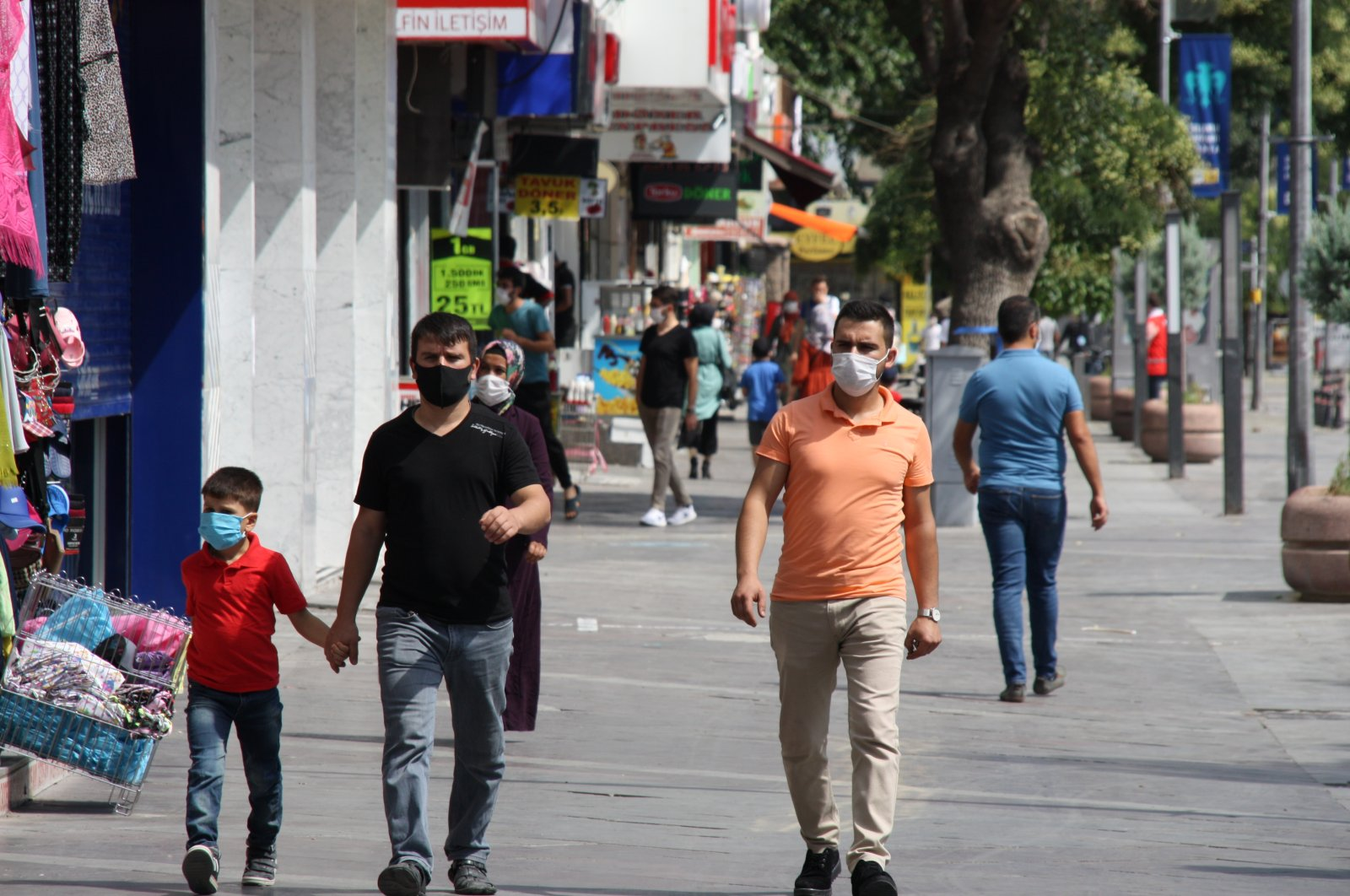 People wearing protective masks walk on a street, in Konya, central Turkey, Aug. 9, 2020. (AA Photo)