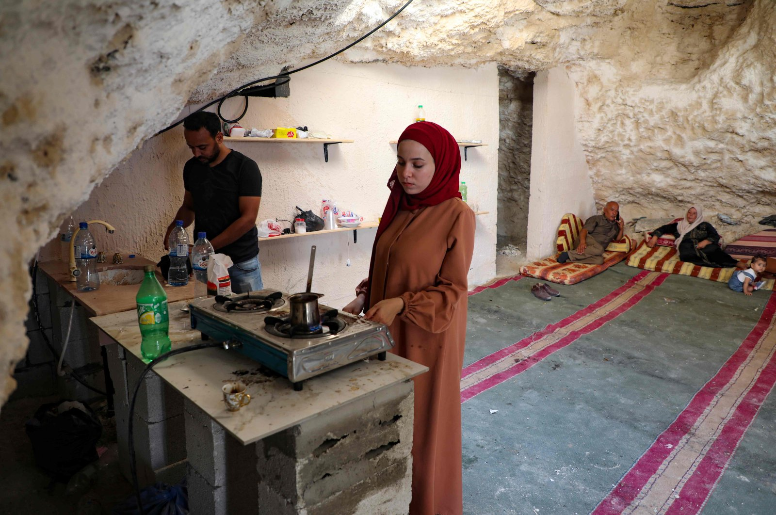 Ahmed Amarneh and his wife prepare coffee at his home, built in a cave in the village of Farasin, west of Jenin, in the northern occupied West Bank, Aug. 4, 2020. (AFP Photo)