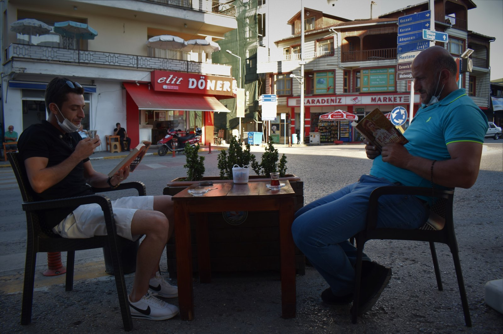Two men read books at a table outside the coffeehouse in Akçakoca district, in Düzce, northern Turkey, Aug. 9, 2020. (AA Photo)