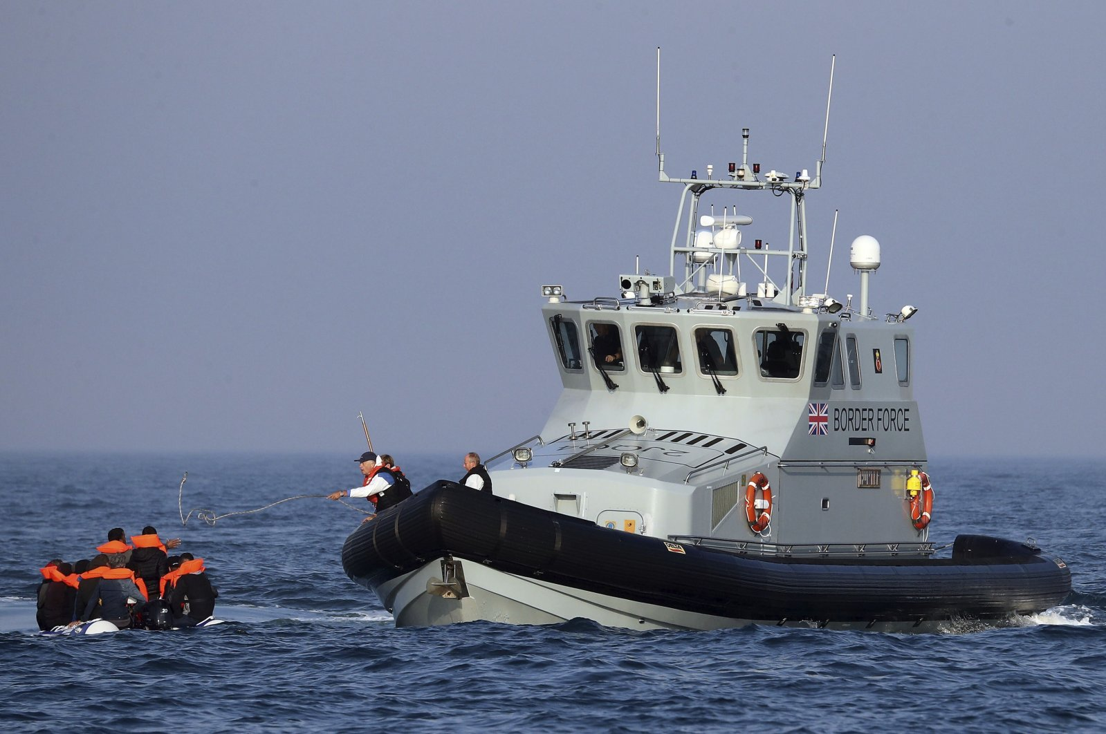 A Border Force vessel assists a group of people thought to be migrants traveling on an inflatable dinghy in the English Channel, Britain, Aug. 10, 2020. (AP Photo)