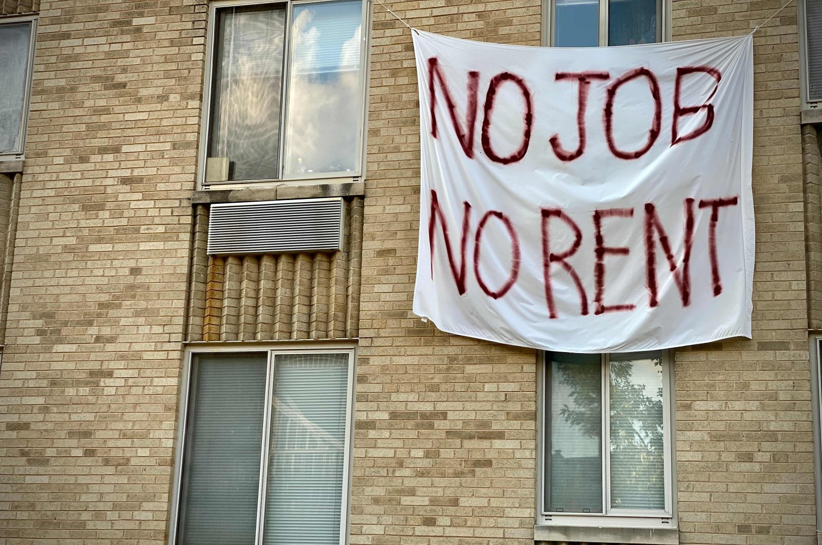 """A banner against renters eviction reading """"no job, no rent"""" is displayed on a controlled rent building in Washington, DC on August 9, 2020. (AFP Photo)"""
