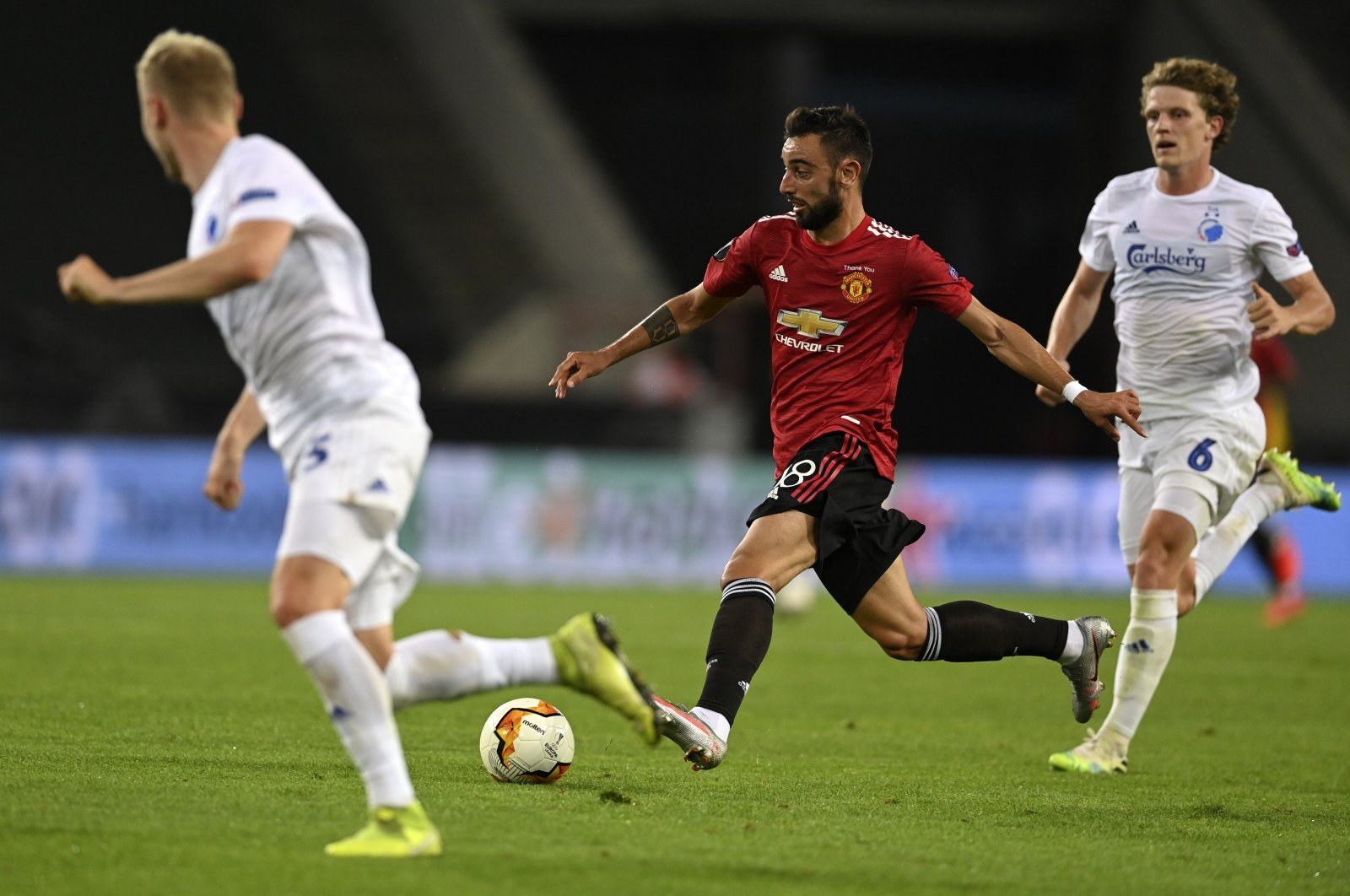 Manchester United's Bruno Fernandes, center, controls the ball during the Europa League quarter-final football match between Manchester United and Copenhagen at the Rhein Energie Stadium in Cologne, Germany, Monday, Aug. 10, 2020. (EPA via AP)