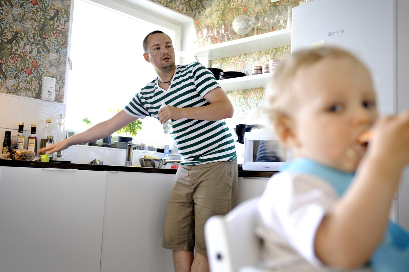 Henrik Holgersson cares for his son, Arvid, in the kitchen of their home in Stockholm, June 29, 2011. (AP Photo)