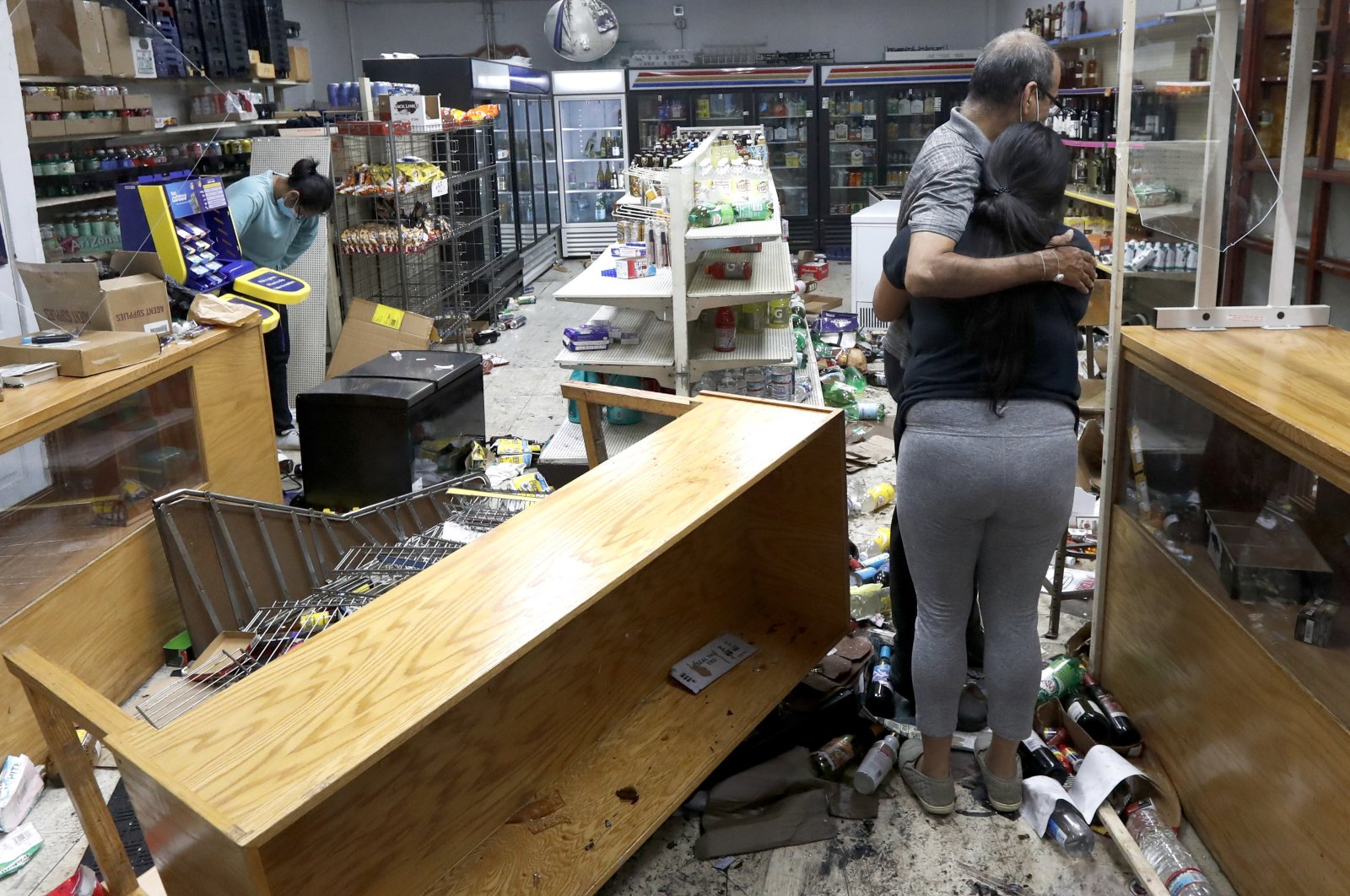 Yogi Dalal (R) hugs his daughter Jigisha as his other daughter Kajal (L) bows her head at the family food and liquor store after it was vandalized in Chicago, Illinois, U.S., Aug. 10, 2020. (AP Photo)
